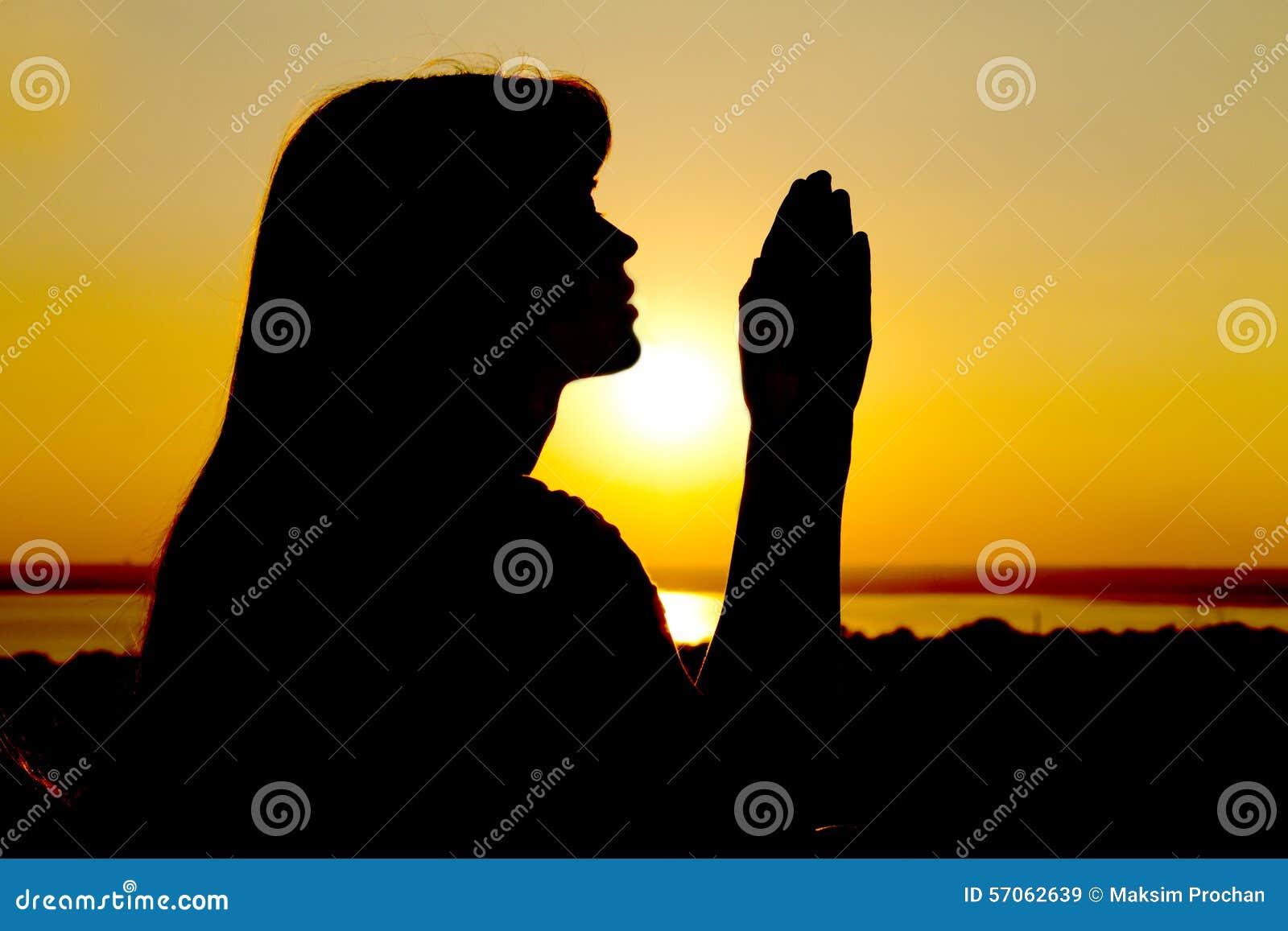 A silhueta de uma menina levanta as mãos para o deus
