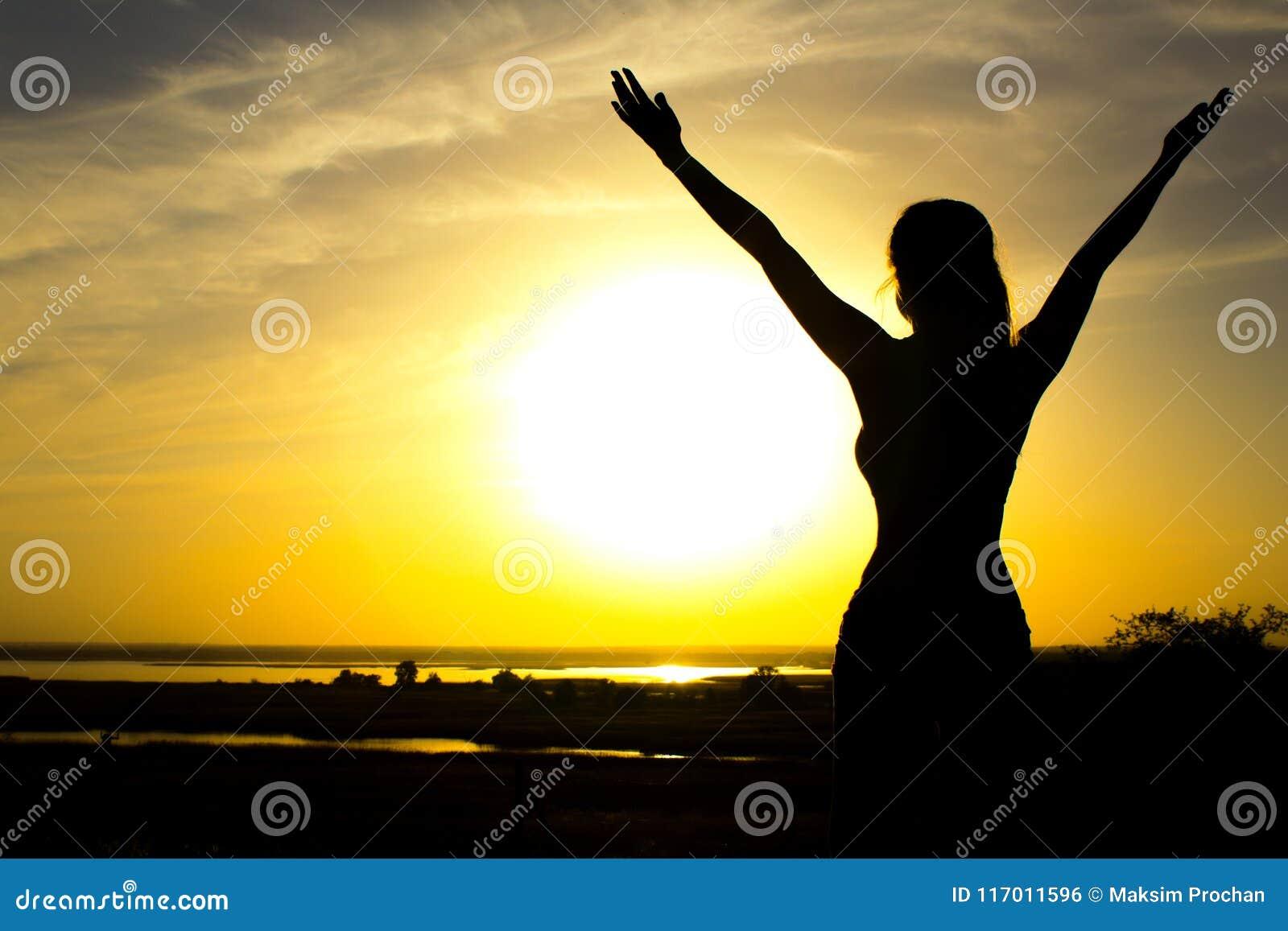 Silhueta de uma menina que levanta as mãos para o céu após o treinamento físico, uma mulher que aprecia o por do sol