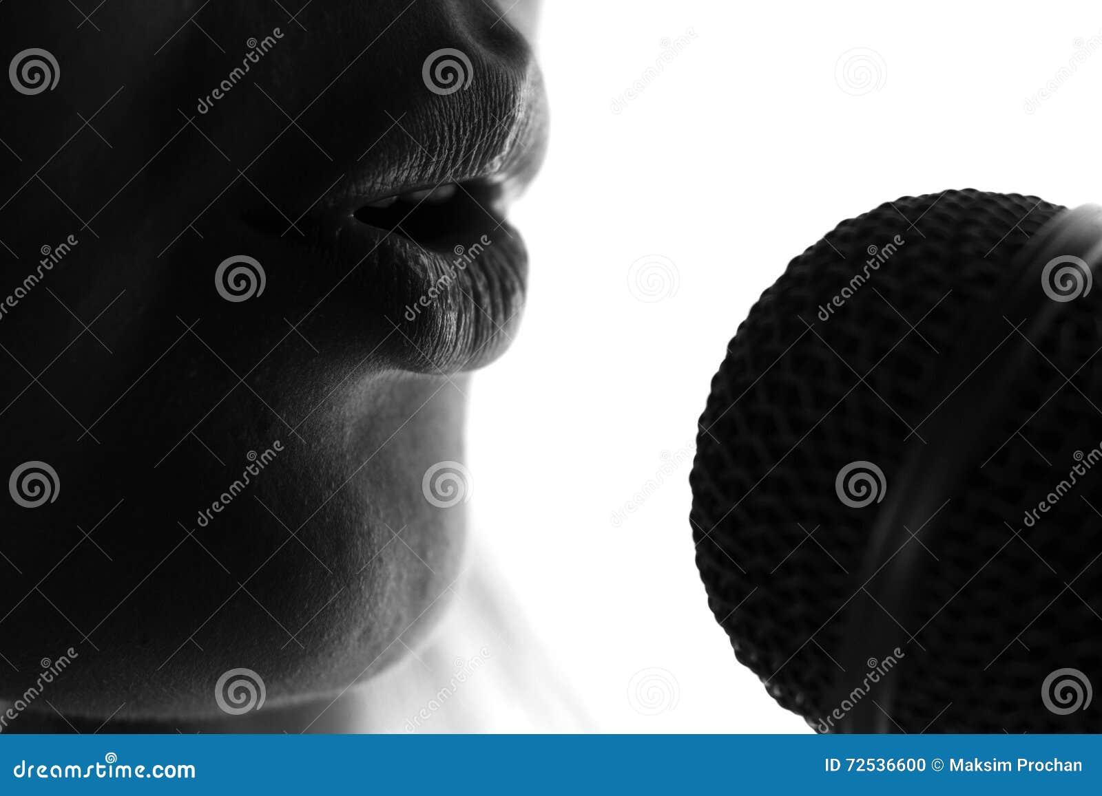 Silhueta de uma mulher que canta com um microfone nas mãos