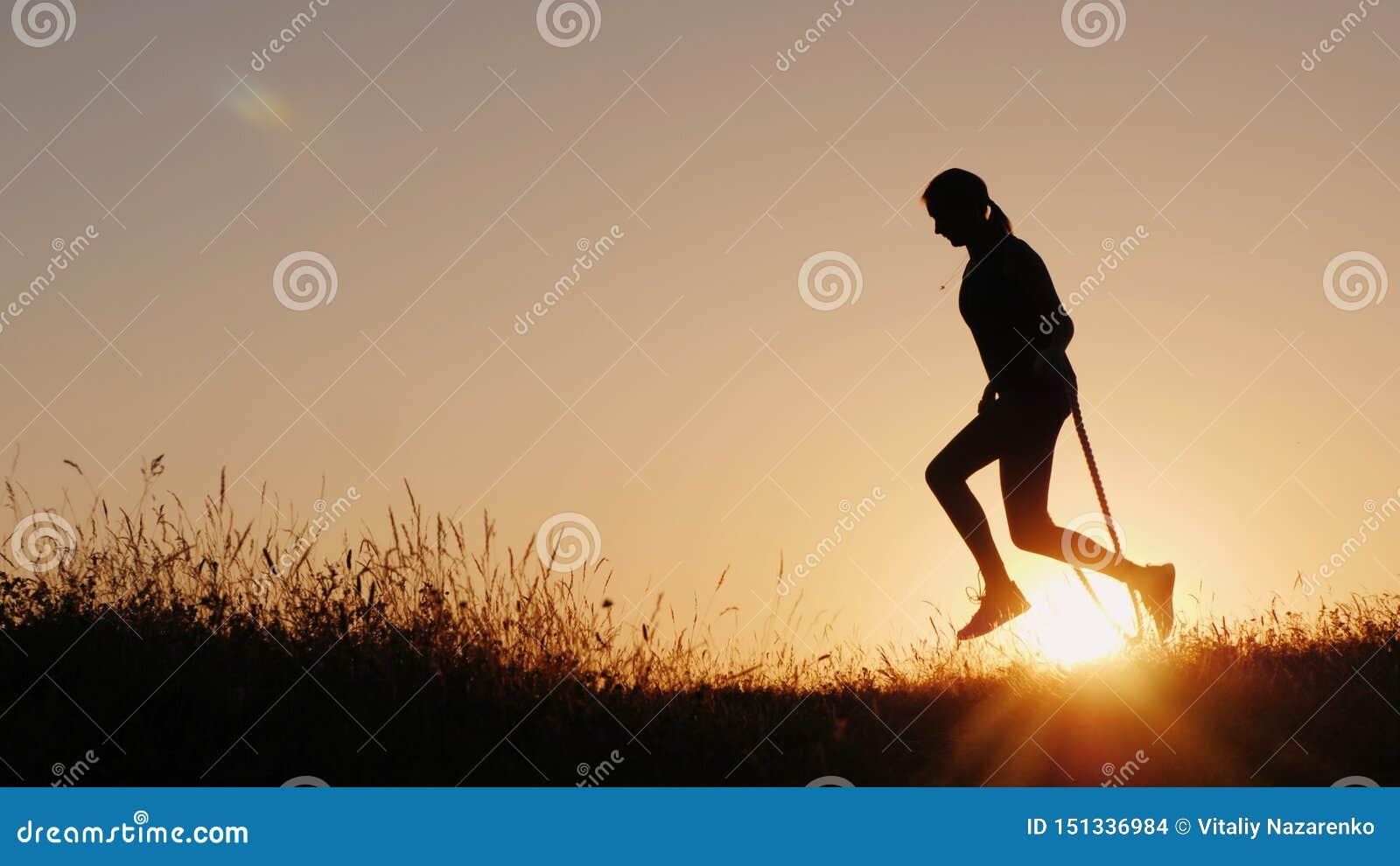 Silhueta de uma mulher - saltando através da corda no por do sol