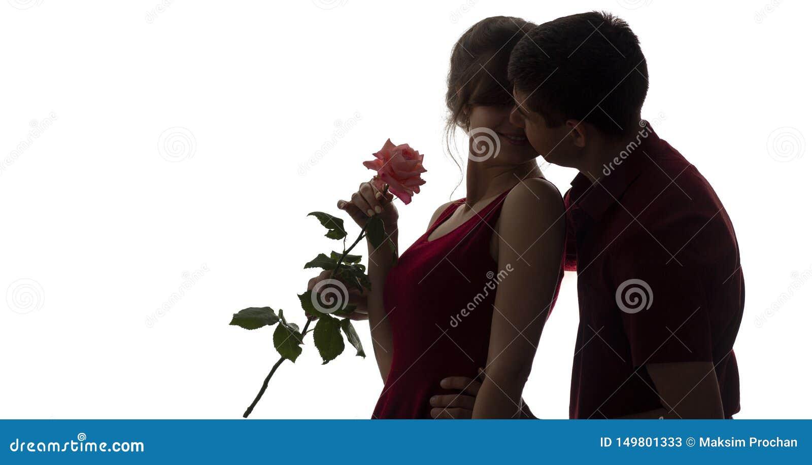 A silhueta de uma queda do homem novo e da mulher no amor no fundo isolado branco, menino veio acima atrás à menina fazer uma sur
