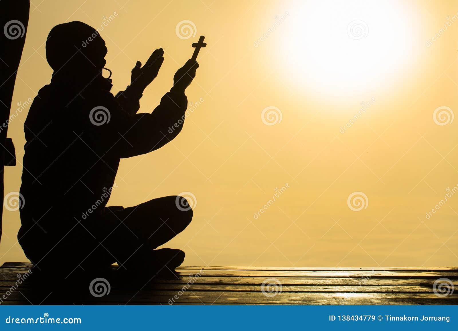 Silhueta do homem novo cristão que reza com uma cruz no nascer do sol, fundo do conceito de Christian Religion