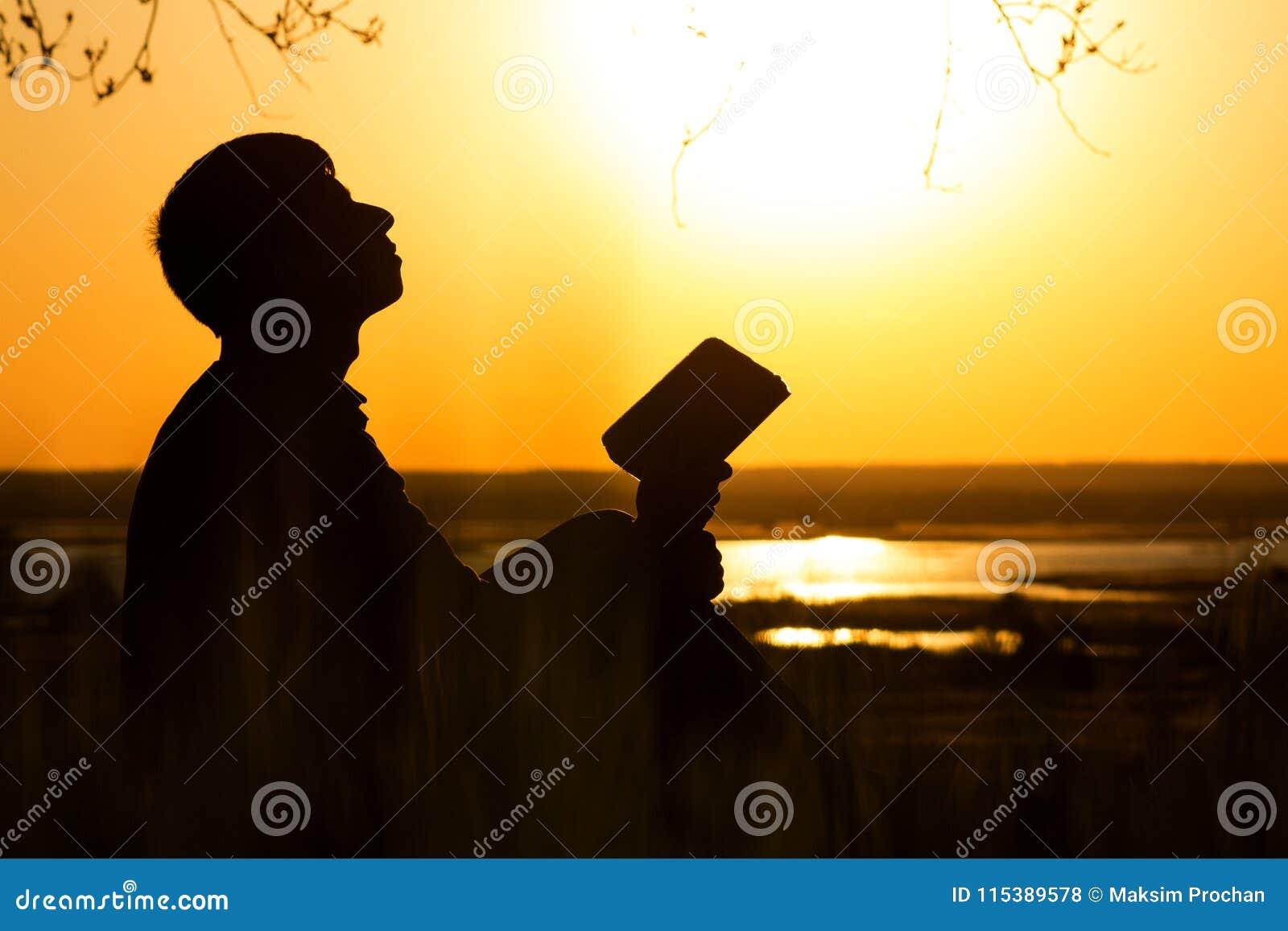 Silhueta do homem que gira para o deus com a esperança, o conceito da fé e a espiritualidade