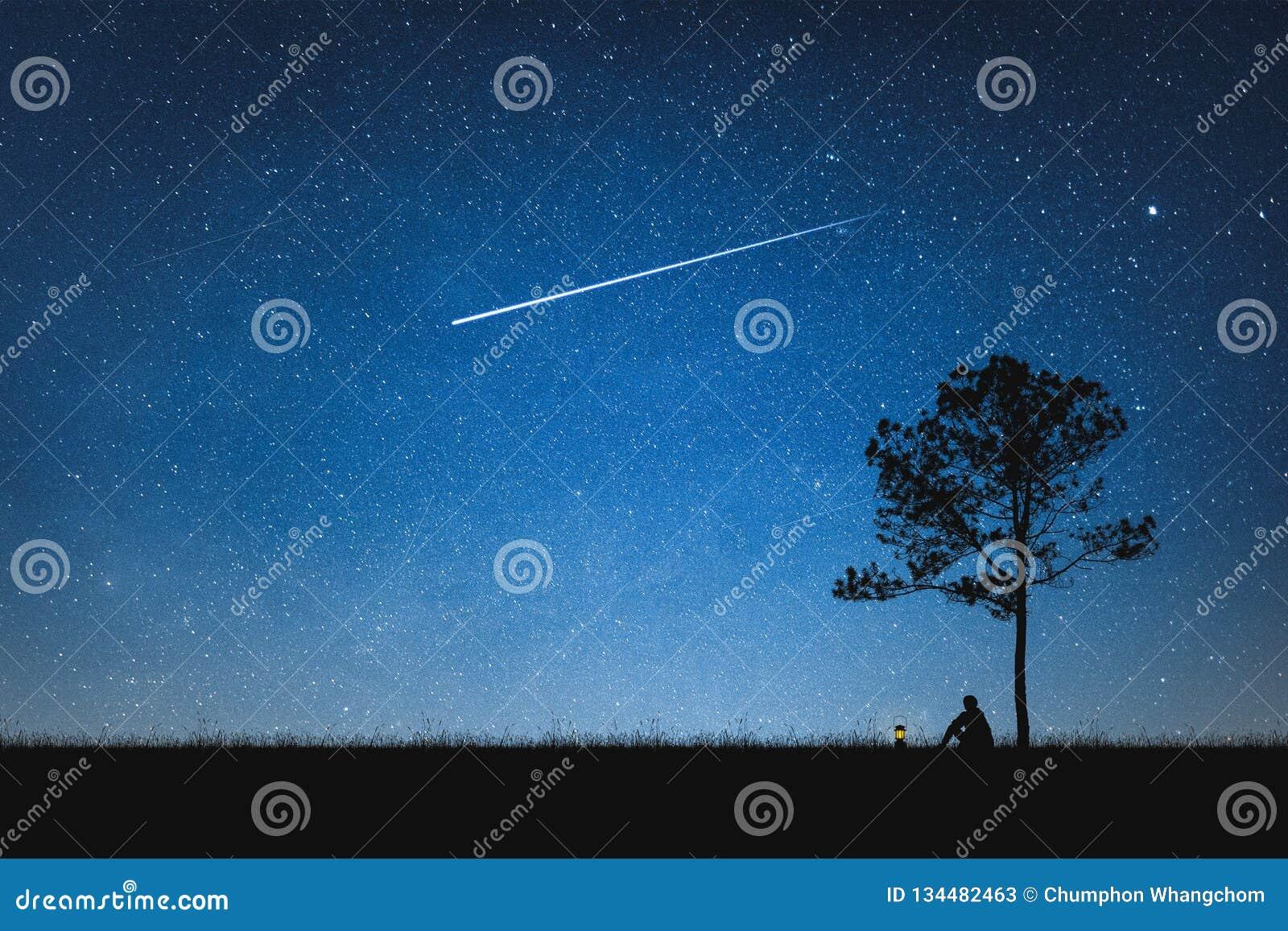 Silhueta do homem que senta-se na montanha e no céu noturno com estrela de tiro conceito sozinho