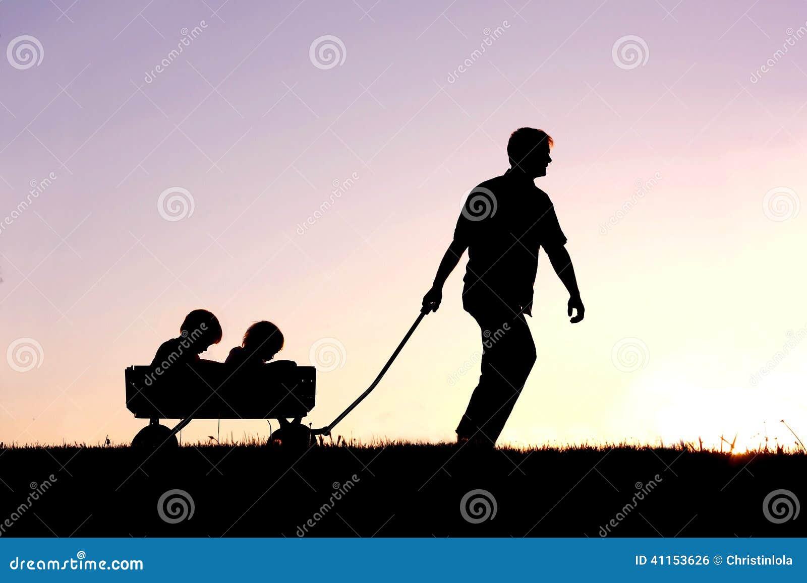 Silhueta do pai Pulling Sons no vagão no por do sol