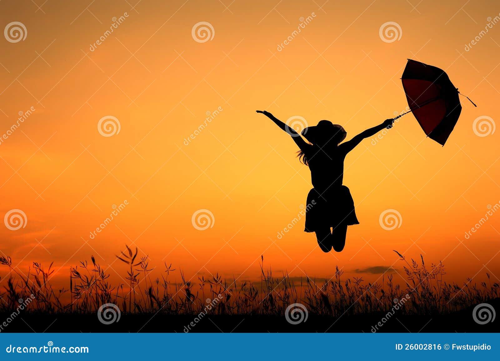 Silhueta do salto e do por do sol da mulher do guarda-chuva