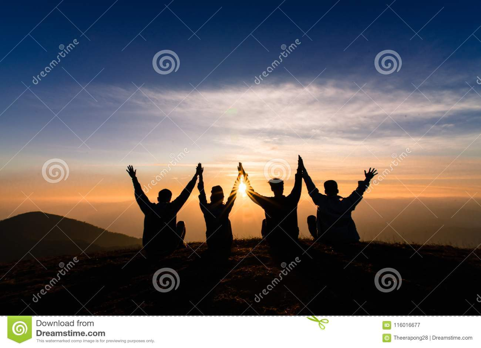 A silhueta dos amigos agita as mãos acima e sentando-se junto no sol