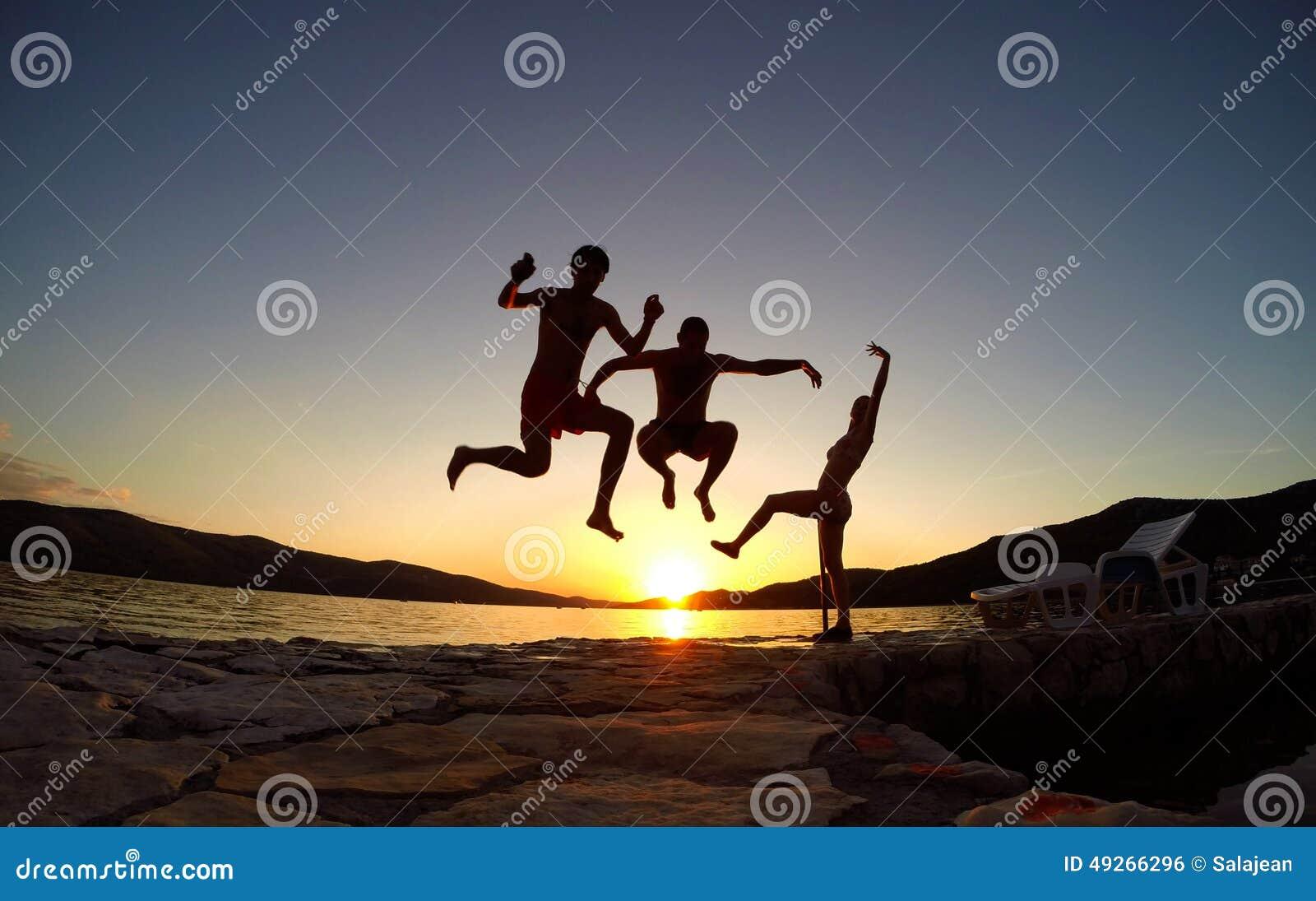 Silhueta dos amigos que saltam no por do sol na praia