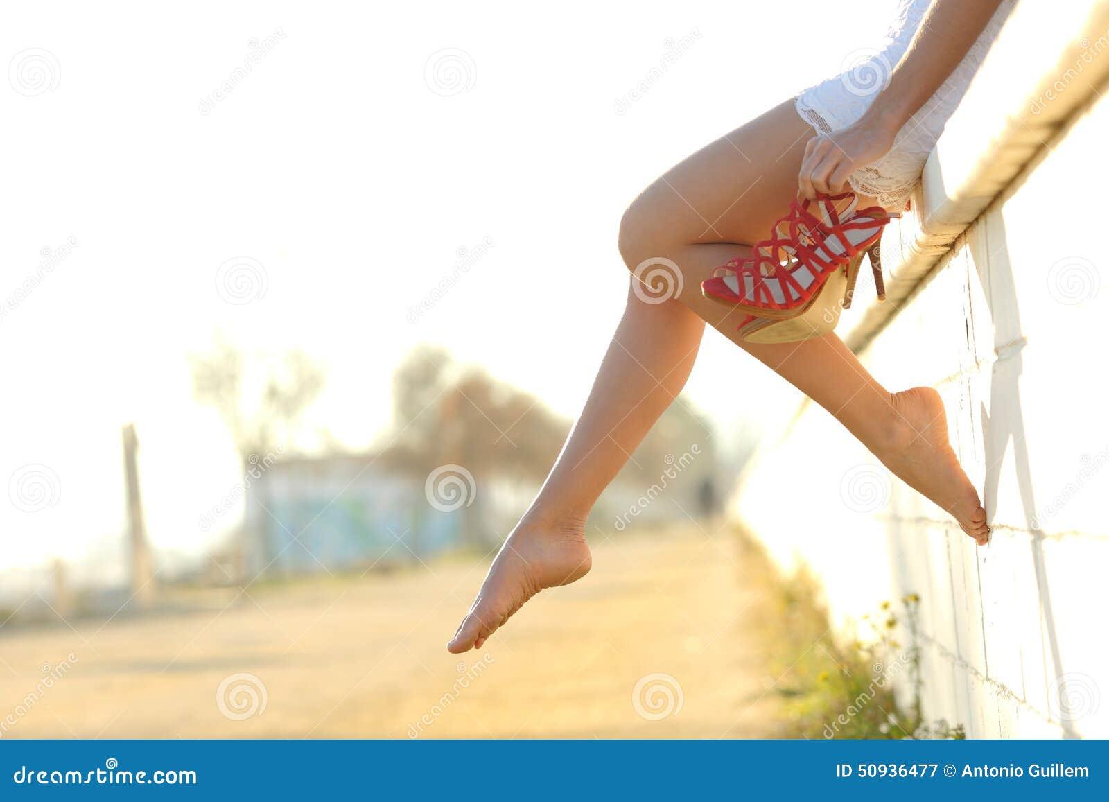 Silhueta dos pés da mulher com suspensão dos saltos de suas mãos
