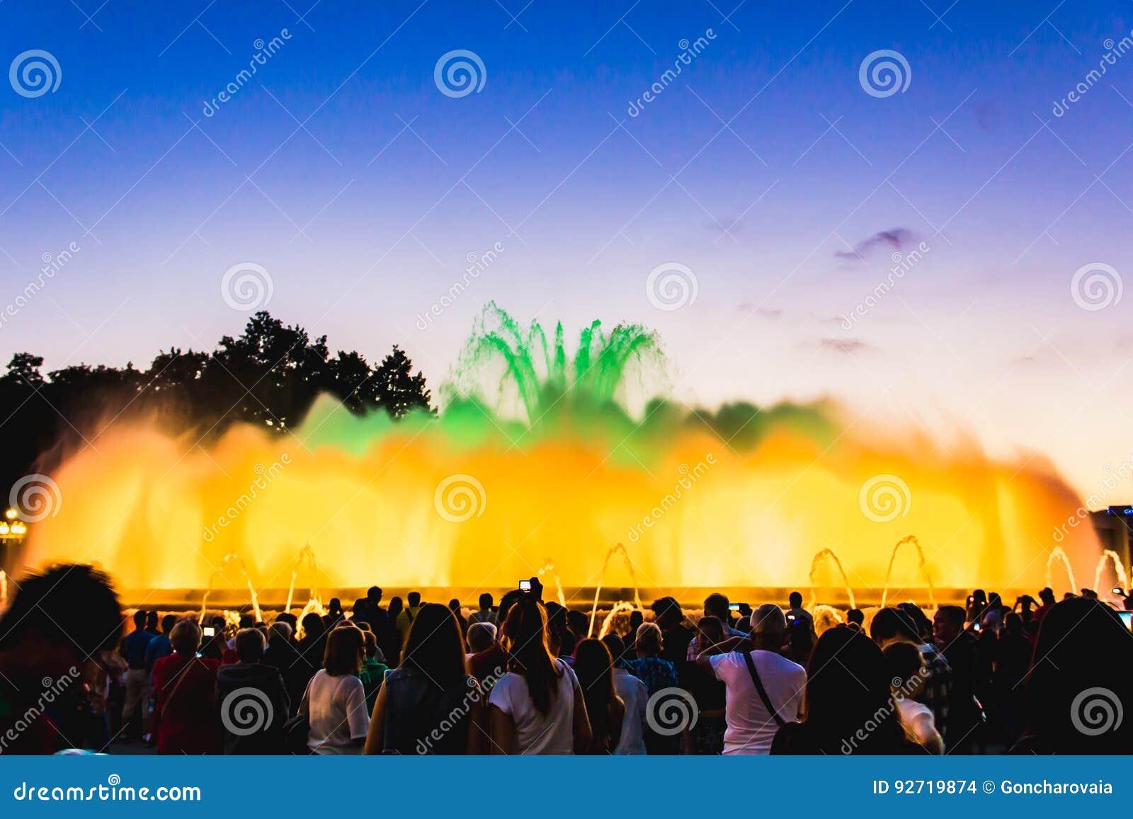 Silhueta dos povos que olham em fontes musicais iluminadas coloridas na noite Desempenho da mostra da noite da luz e da água