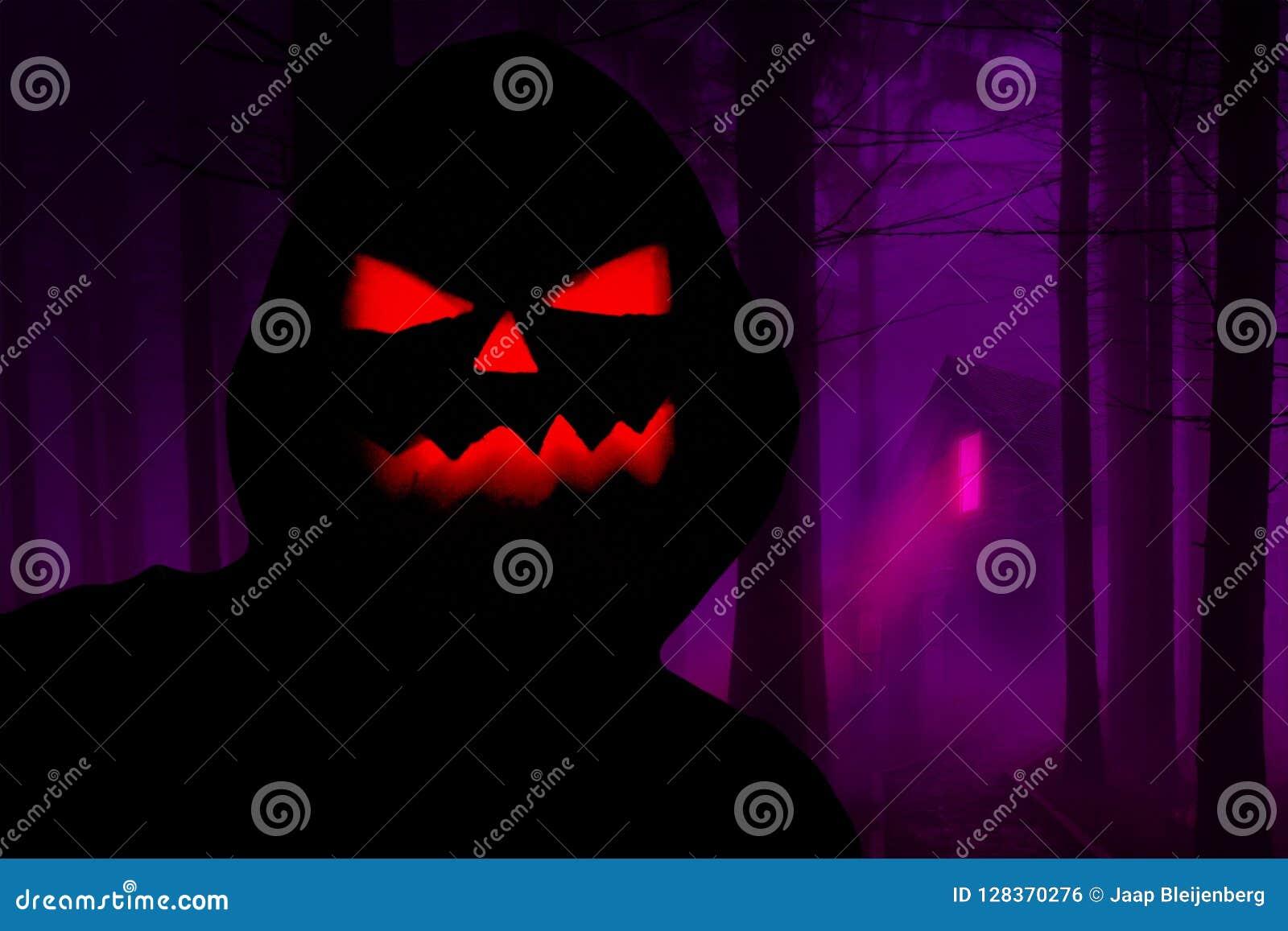 Silhueta encapuçado assustador de Dia das Bruxas com uma cara má da abóbora que está em uma floresta do horror com uma casa assom