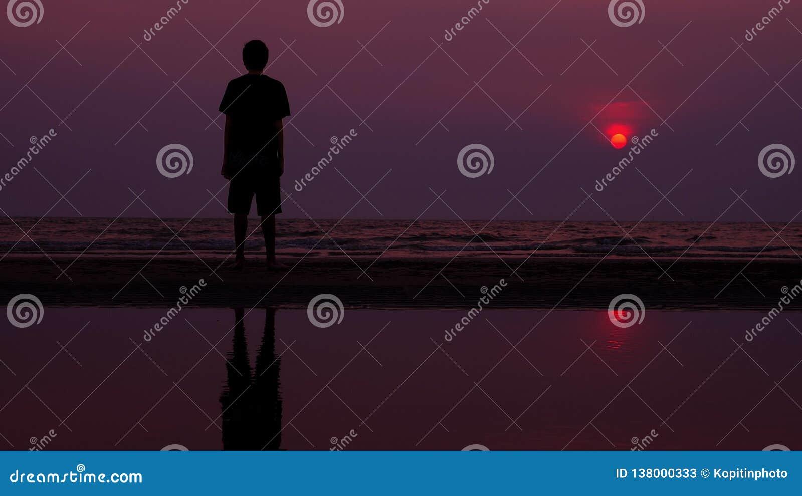 Silhueta Homem novo asiático só que anda pacificamente ao longo de uma praia abandonada no por do sol Seascape
