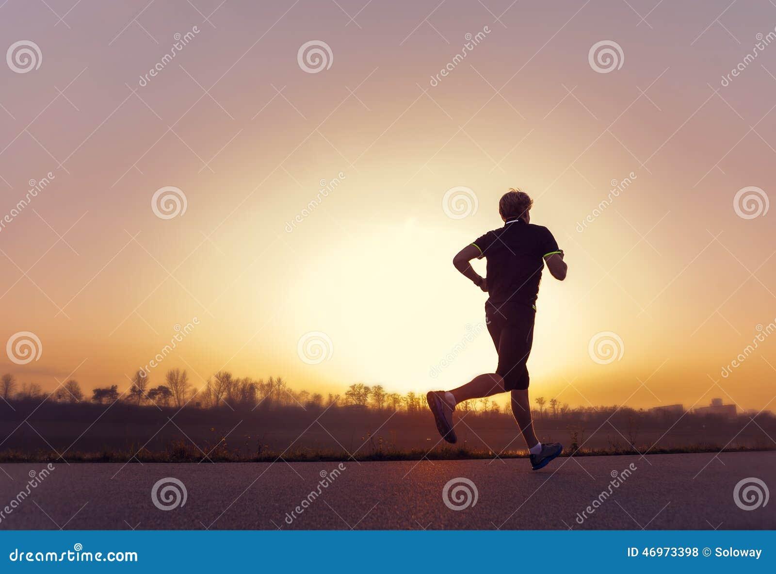 Silhueta running do homem no tempo do por do sol