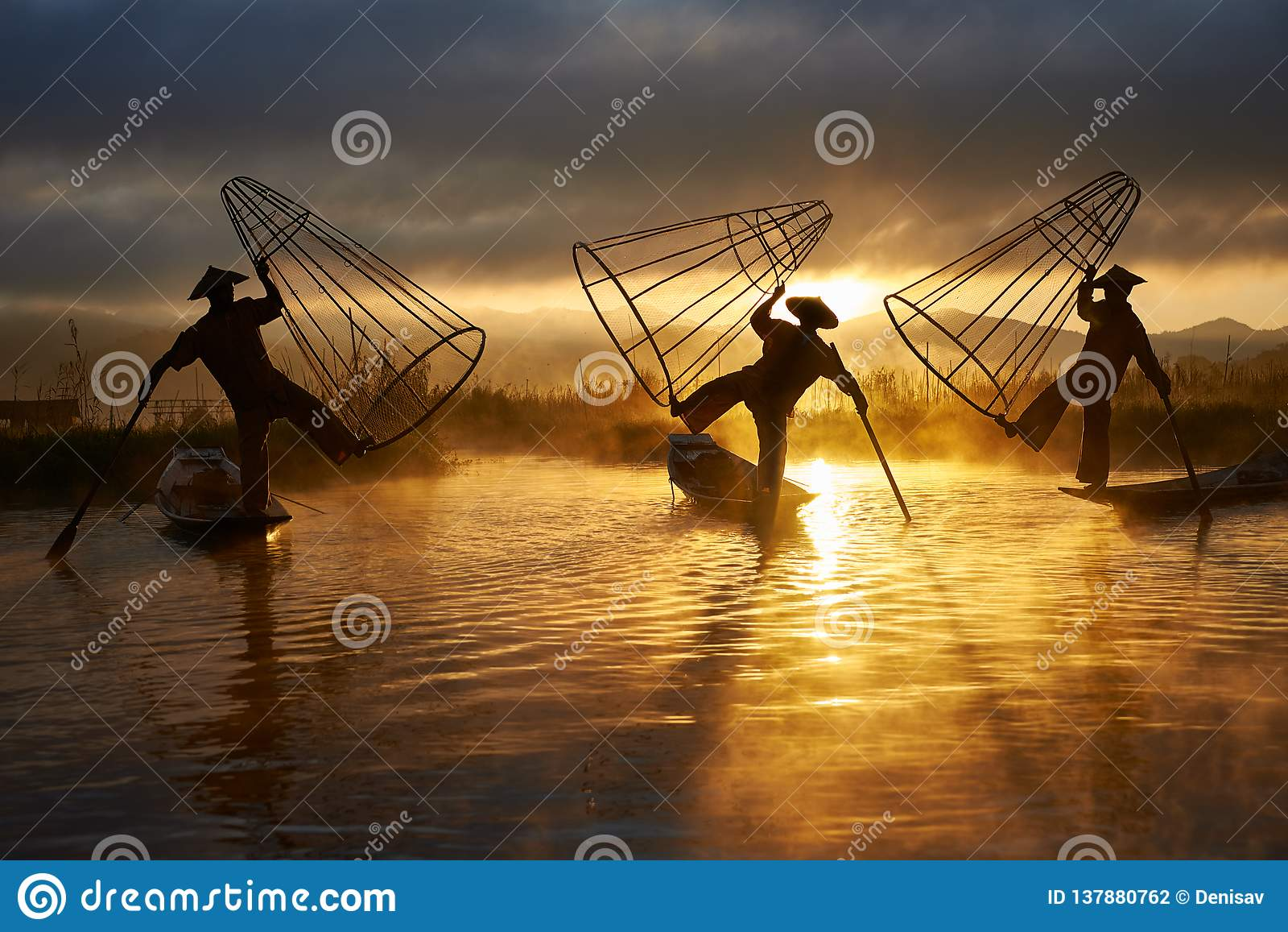 Silhuetas de três pescadores no lago Myanmar Inle