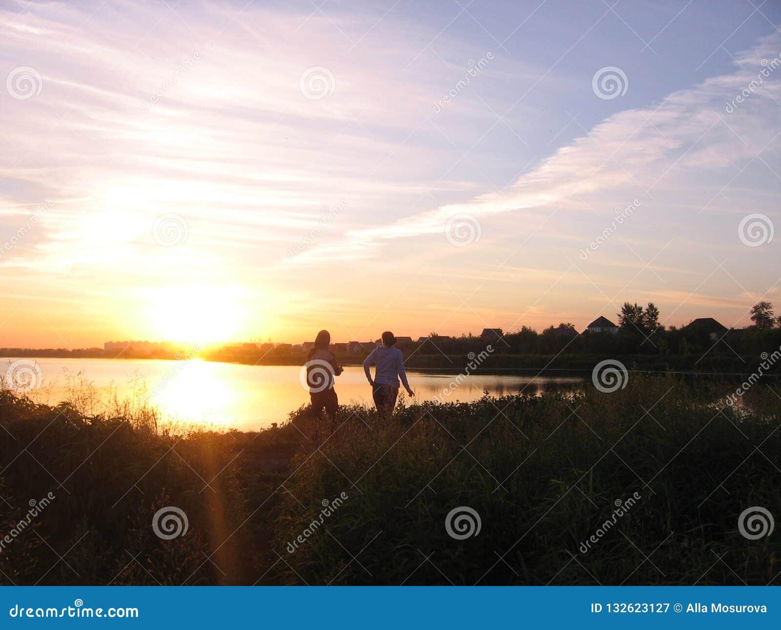 Silhuetas de um homem e de uma menina no lago nos raios do sol de ajuste