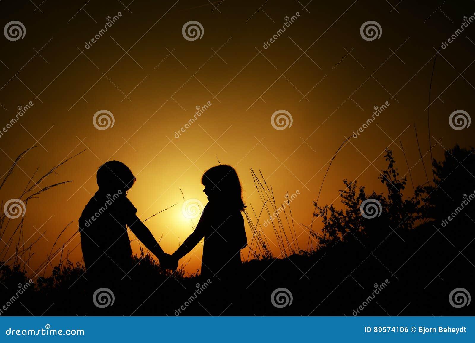 Silhuetas de um menino e de uma menina que guardam as mãos