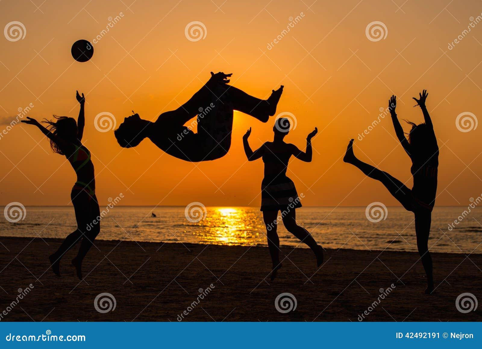 Silhuetas de um pessoa que tem o divertimento em uma praia