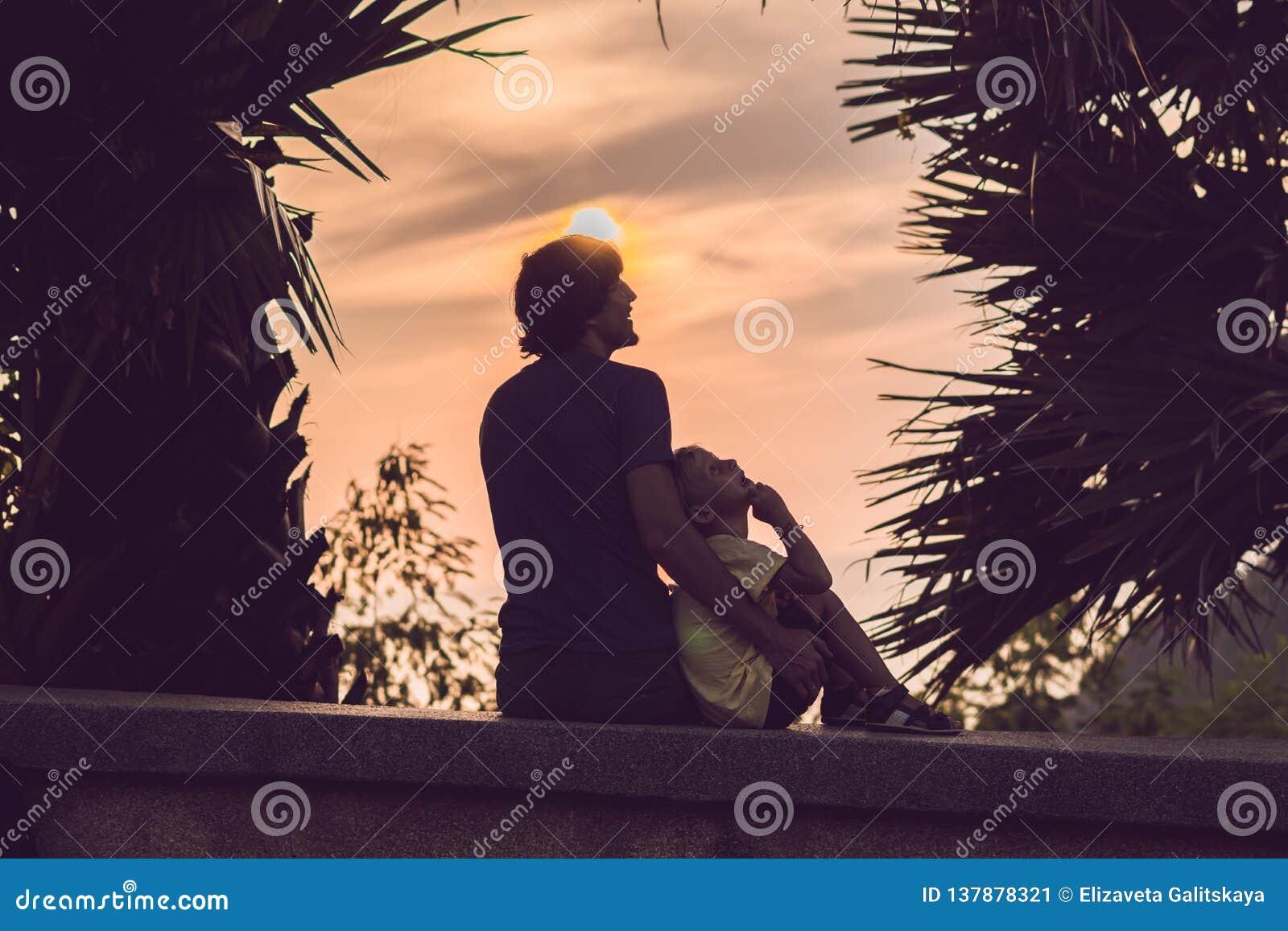 Silhuetas do pai e do filho, que encontram o por do sol nos trópicos contra o contexto das palmeiras