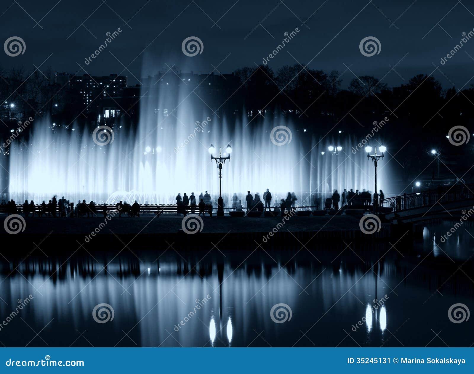 Silhuetas dos povos da noite da fonte