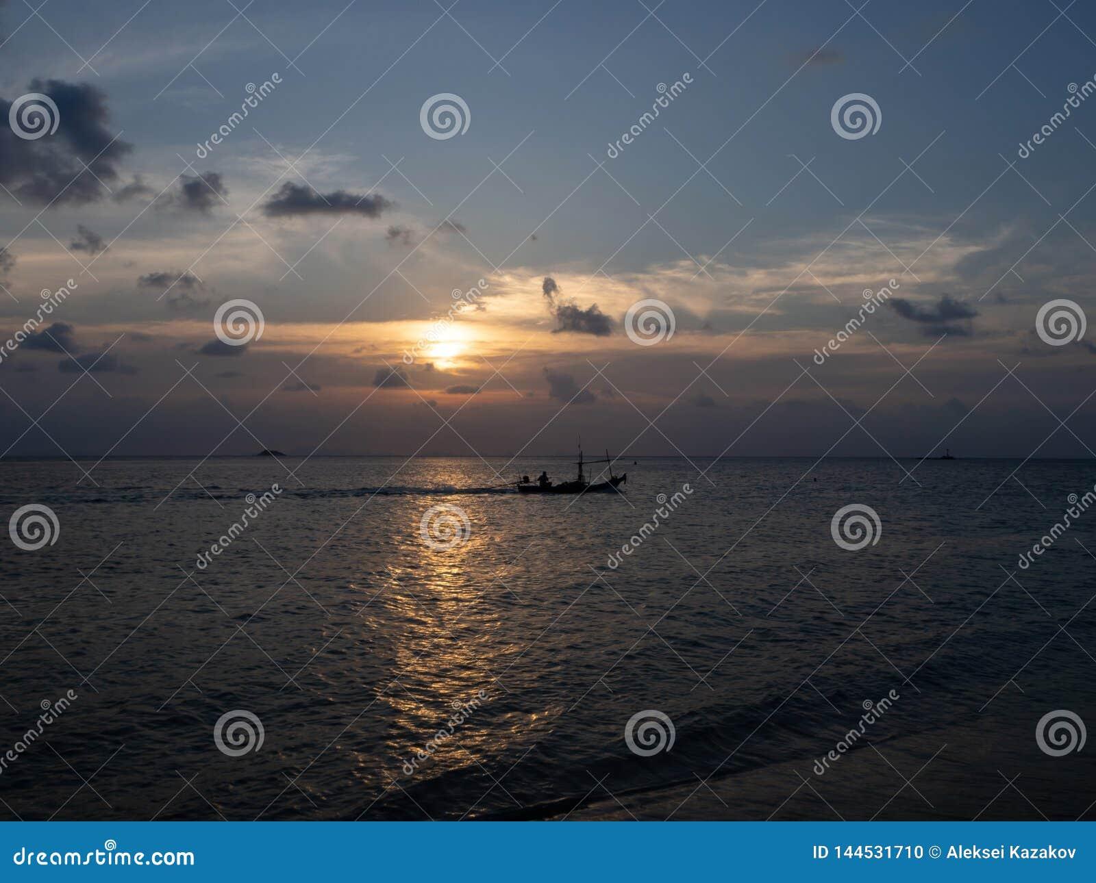 Silhuetas dos povos em um caiaque nos raios do sol de ajuste na perspectiva das nuvens