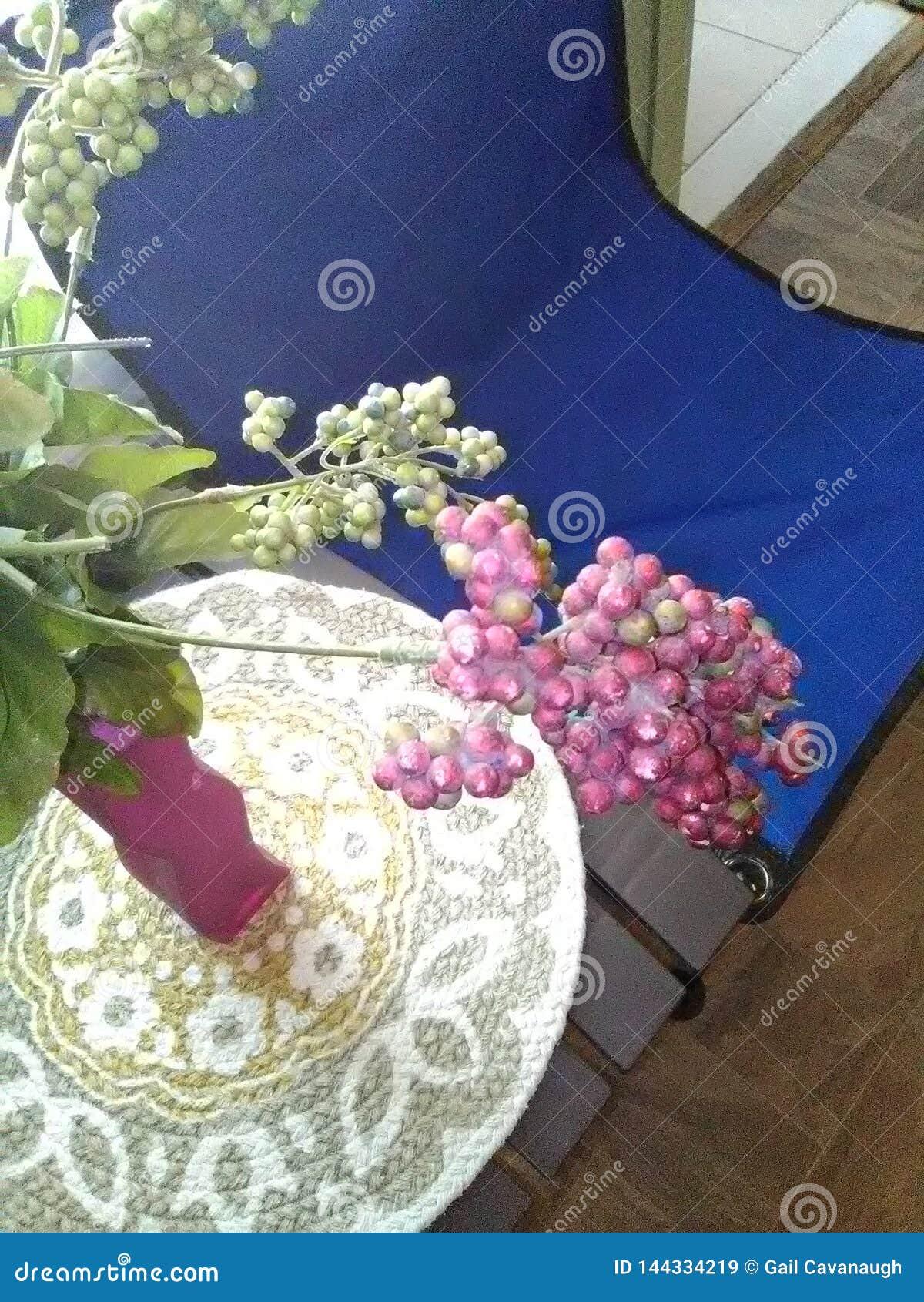 Silla azul de la lona al lado de la tabla cubierta con la estera y el florero tejidos