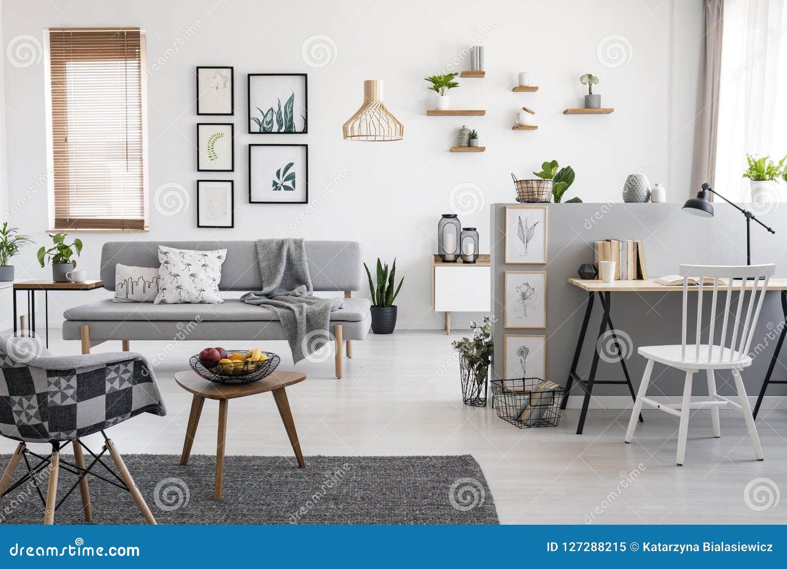 Silla blanca en el escritorio en interior espacioso del apartamento con la galería sobre el sofá gris cerca de la ventana Foto ve