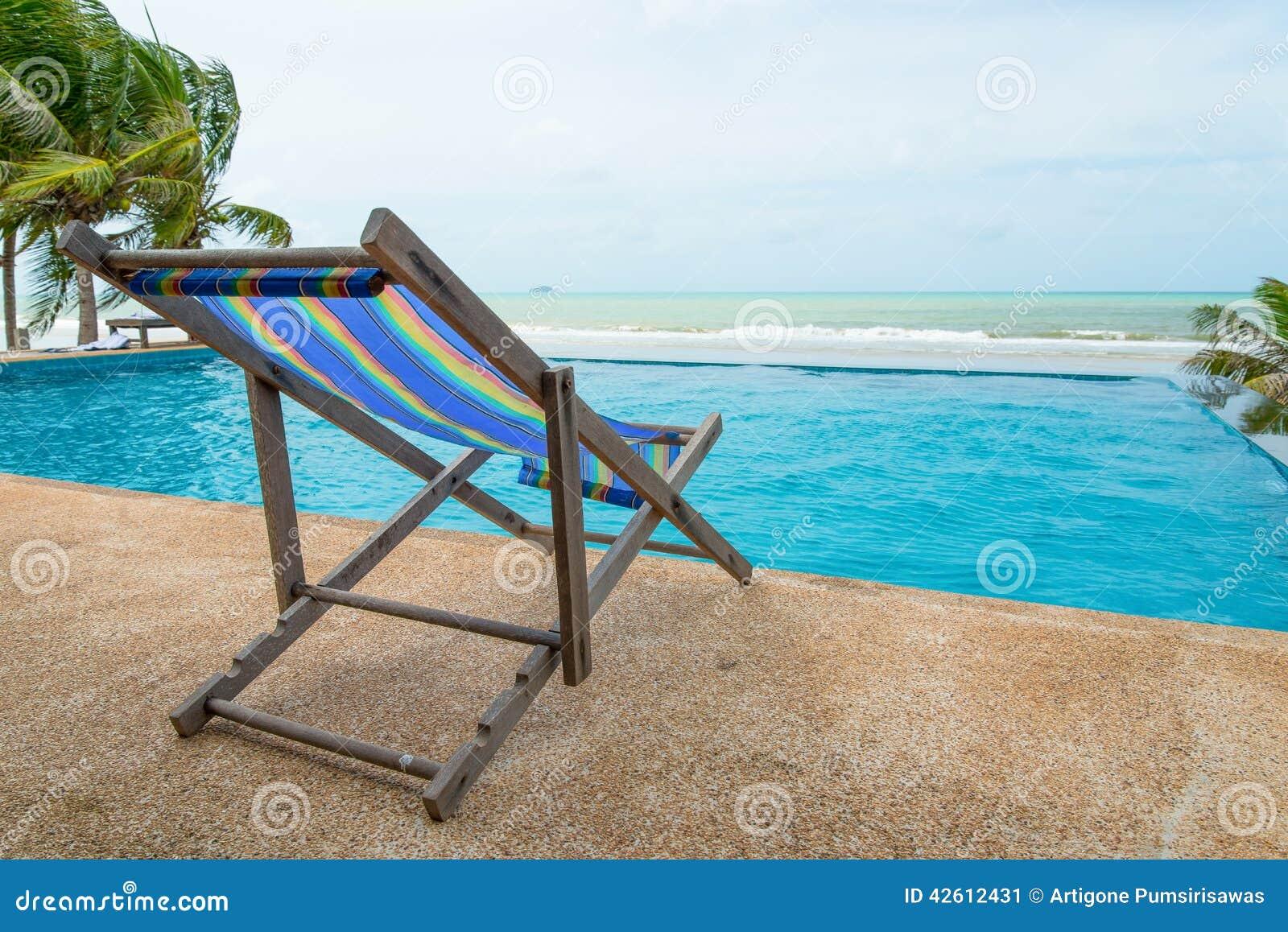 Silla cerca de la piscina y del mar foto de archivo for Sillas para piscina