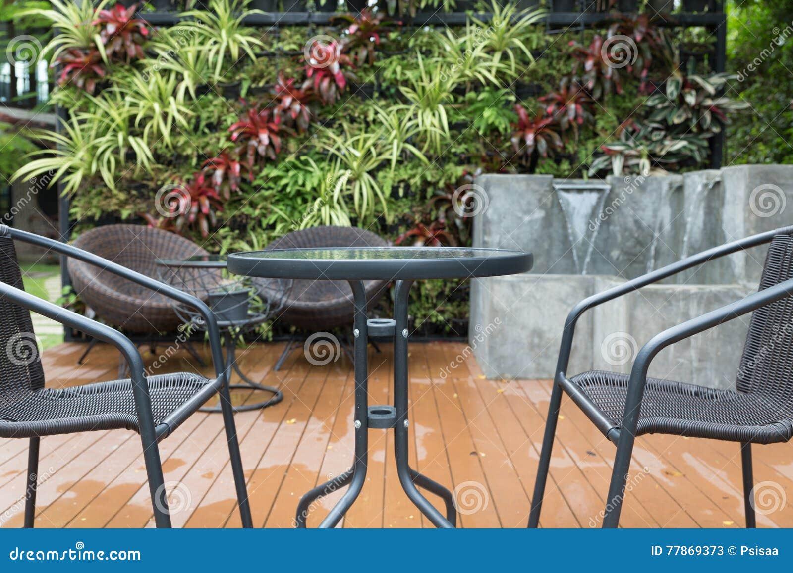 Silla de mimbre y escritorio de la rota en patio imagen de - Sillas de patio ...
