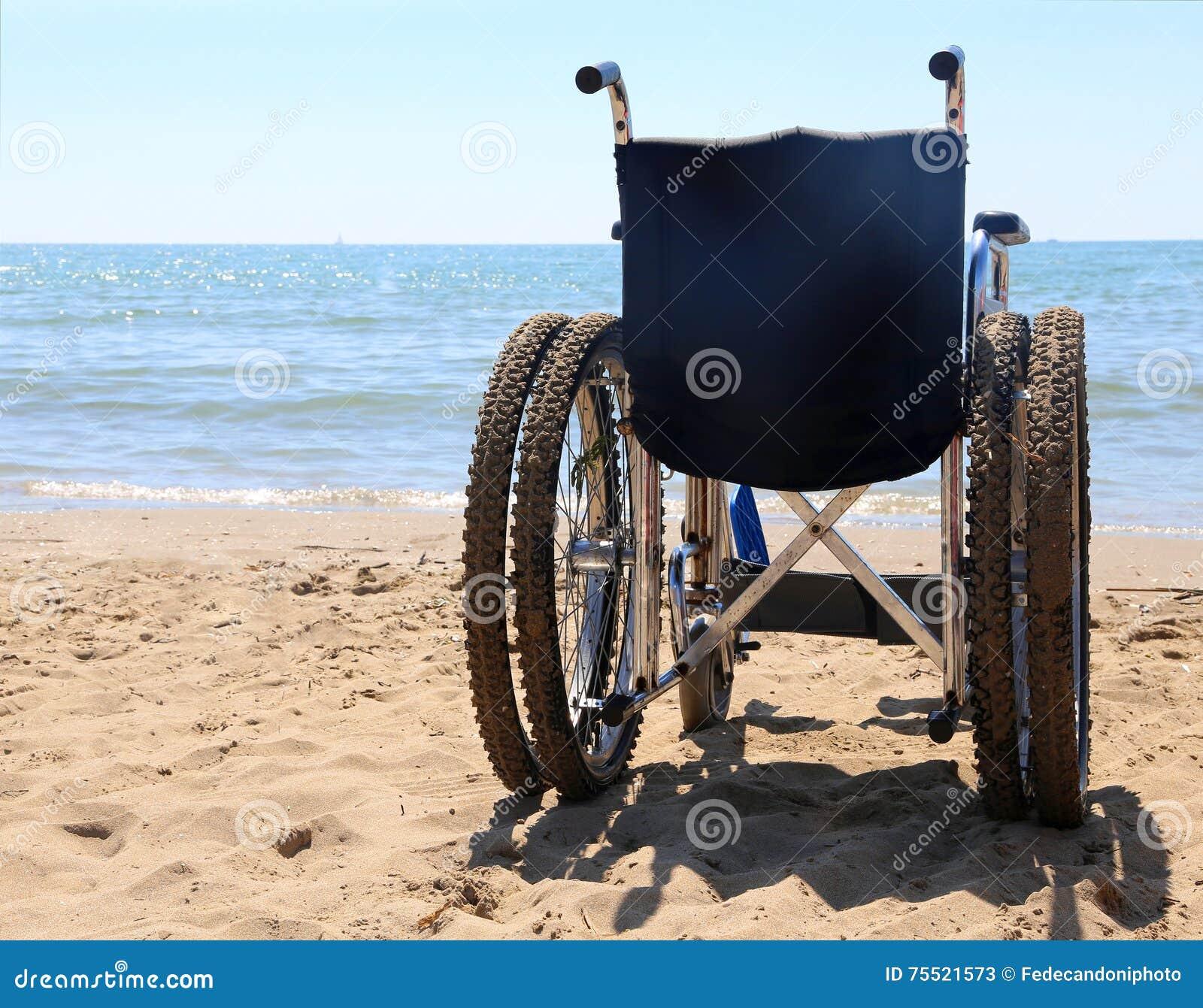 Silla de ruedas en la arena de la playa foto de archivo for Arena de playa precio