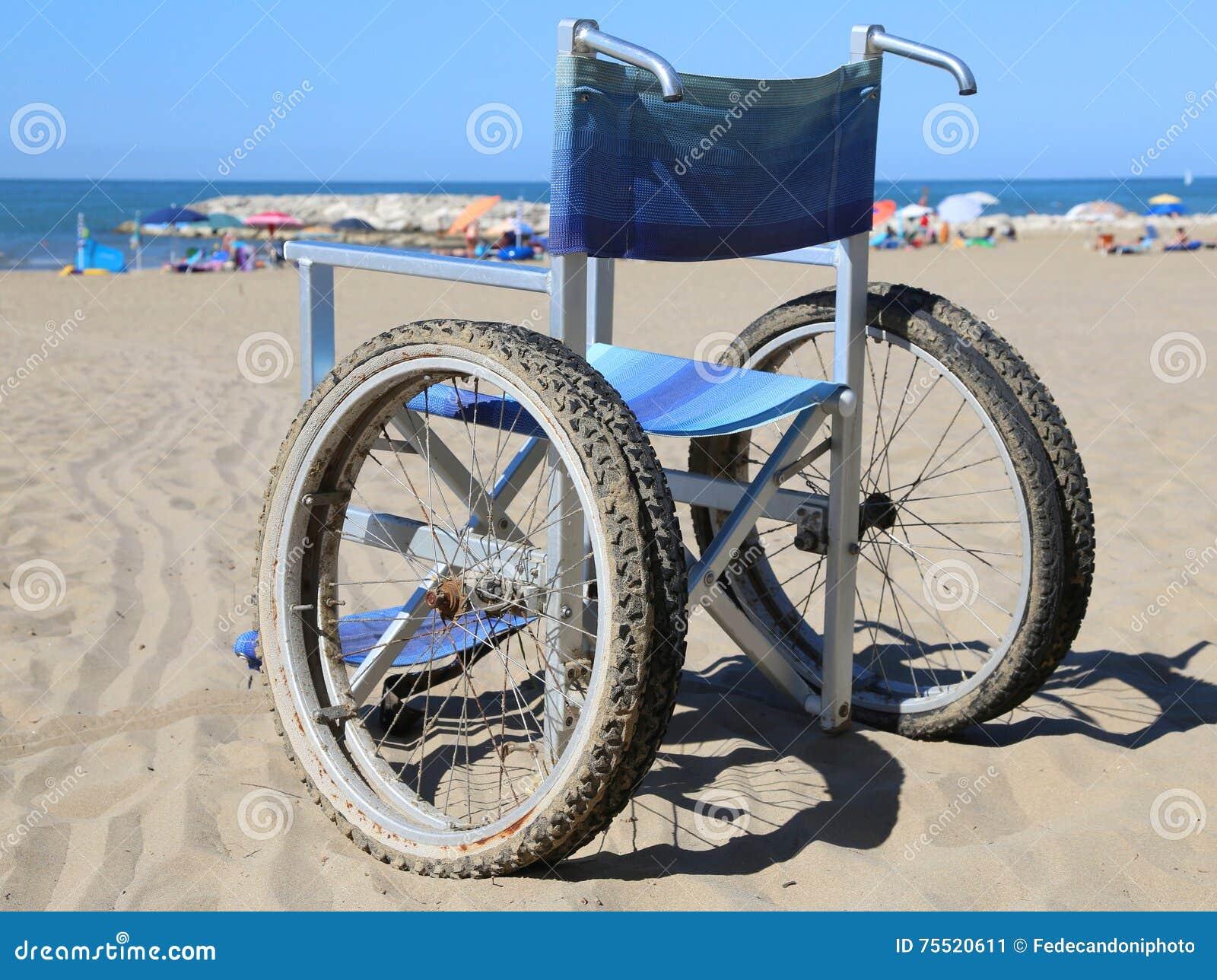 Silla de ruedas en la arena de la playa cerca del mar foto for Arena de playa precio