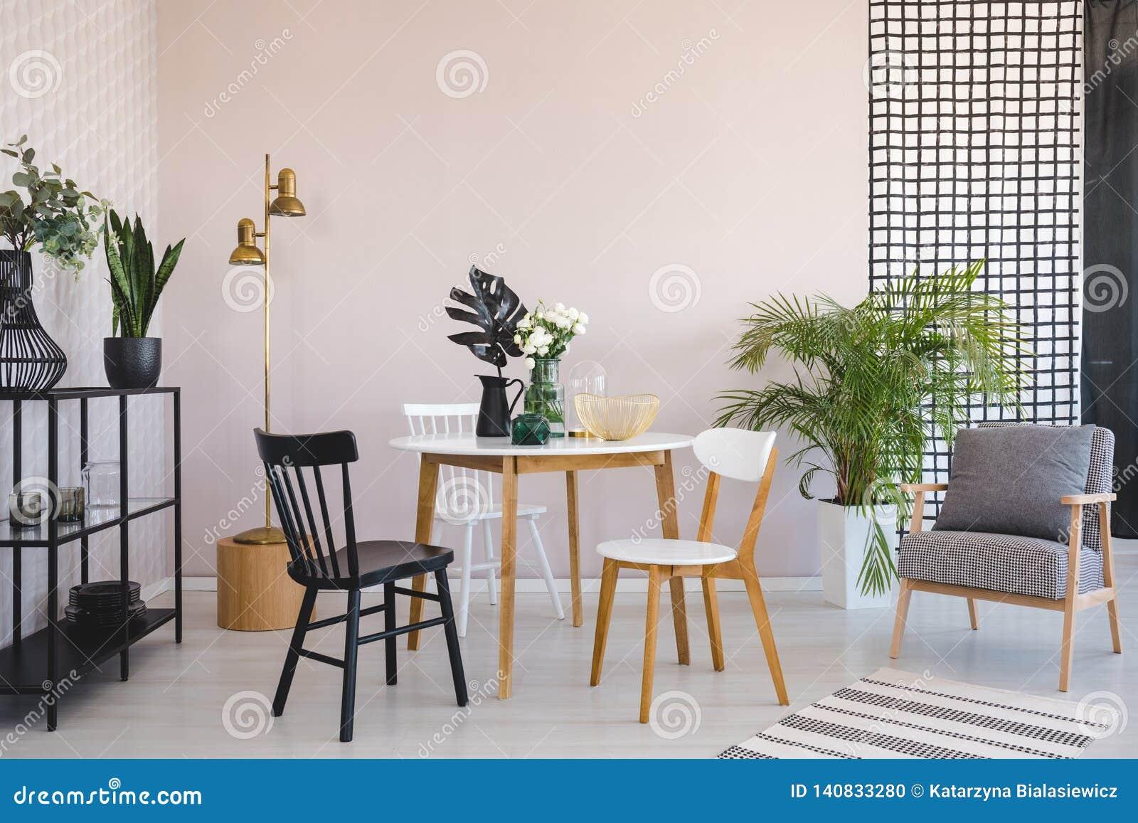 Silla en la tabla de madera con las flores en el comedor interior con la lámpara de la butaca y del oro Foto verdadera