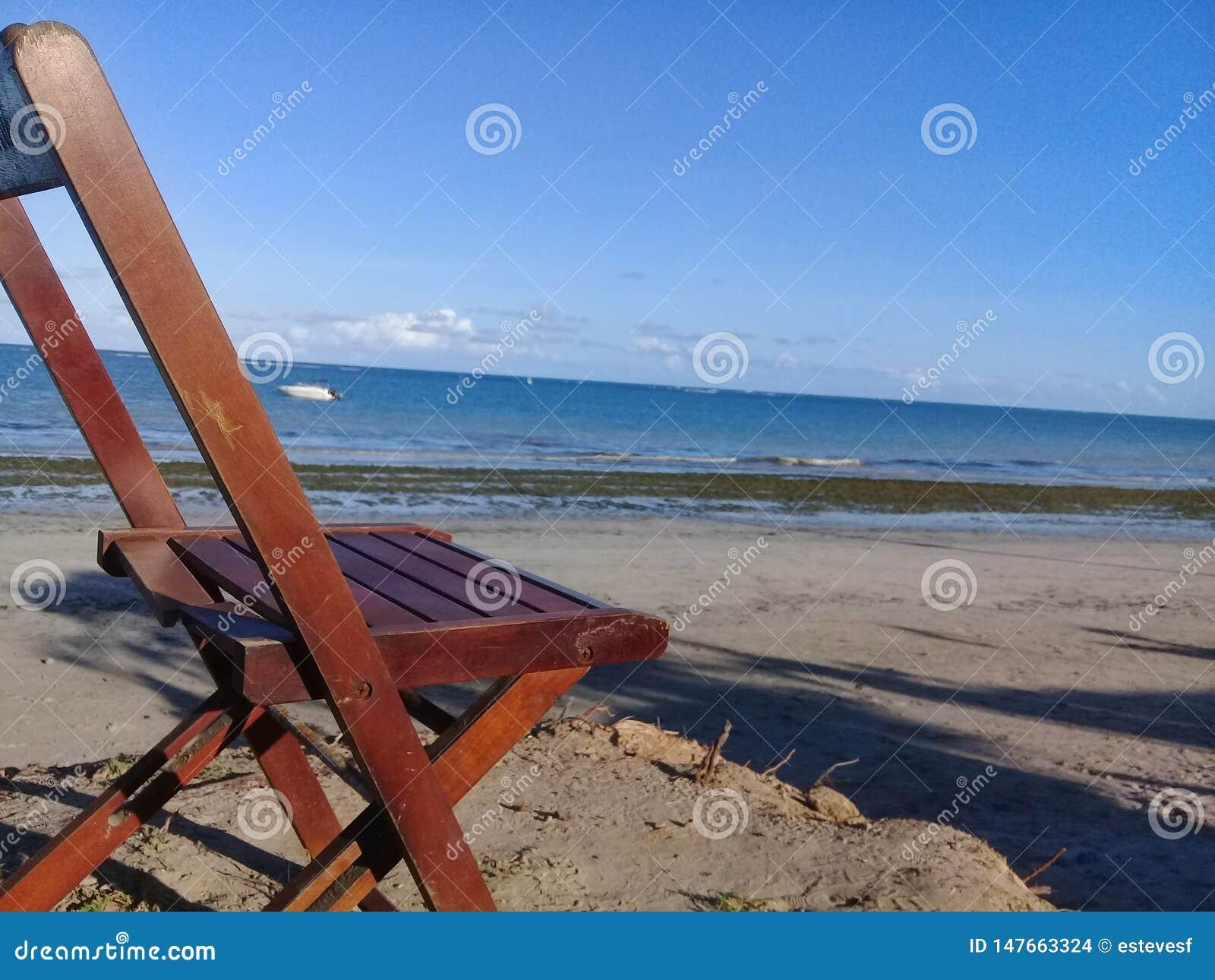Silla quebrada en la playa y un barco detrás