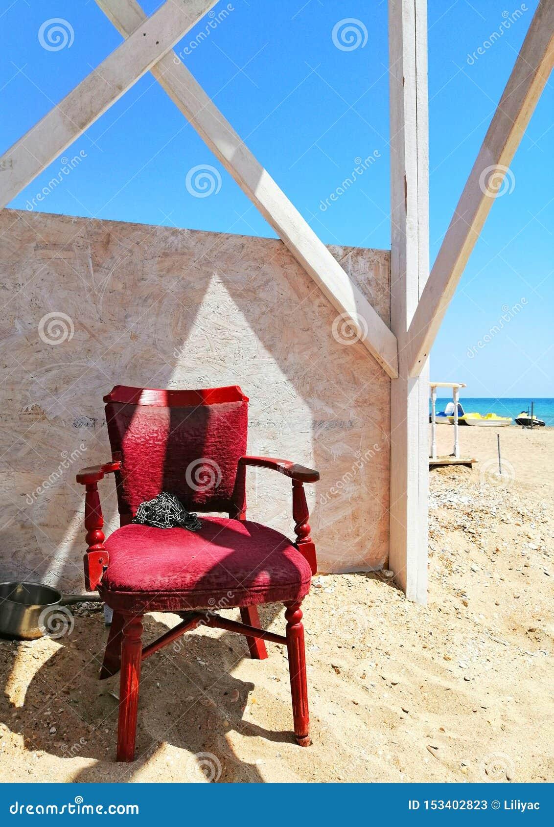 Silla roja vieja en la playa