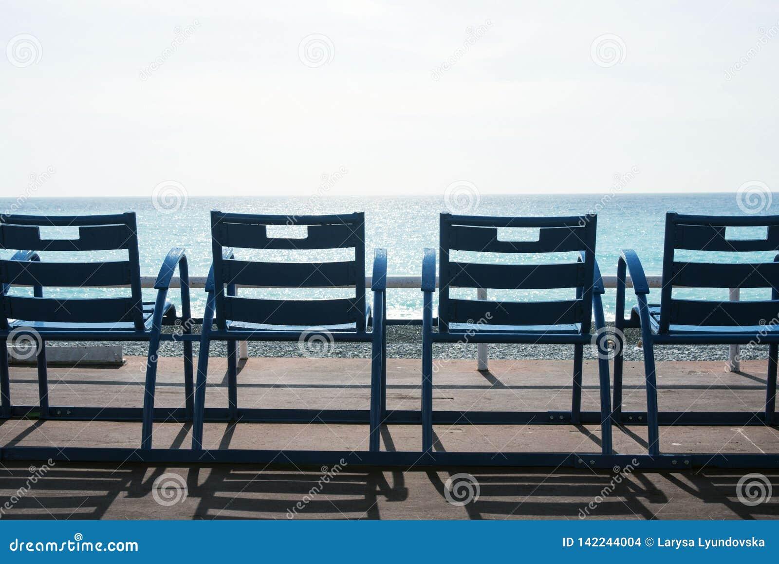 Sillas azules famosas en Promenade des Anglais de Niza, Francia contra el contexto del mar azul