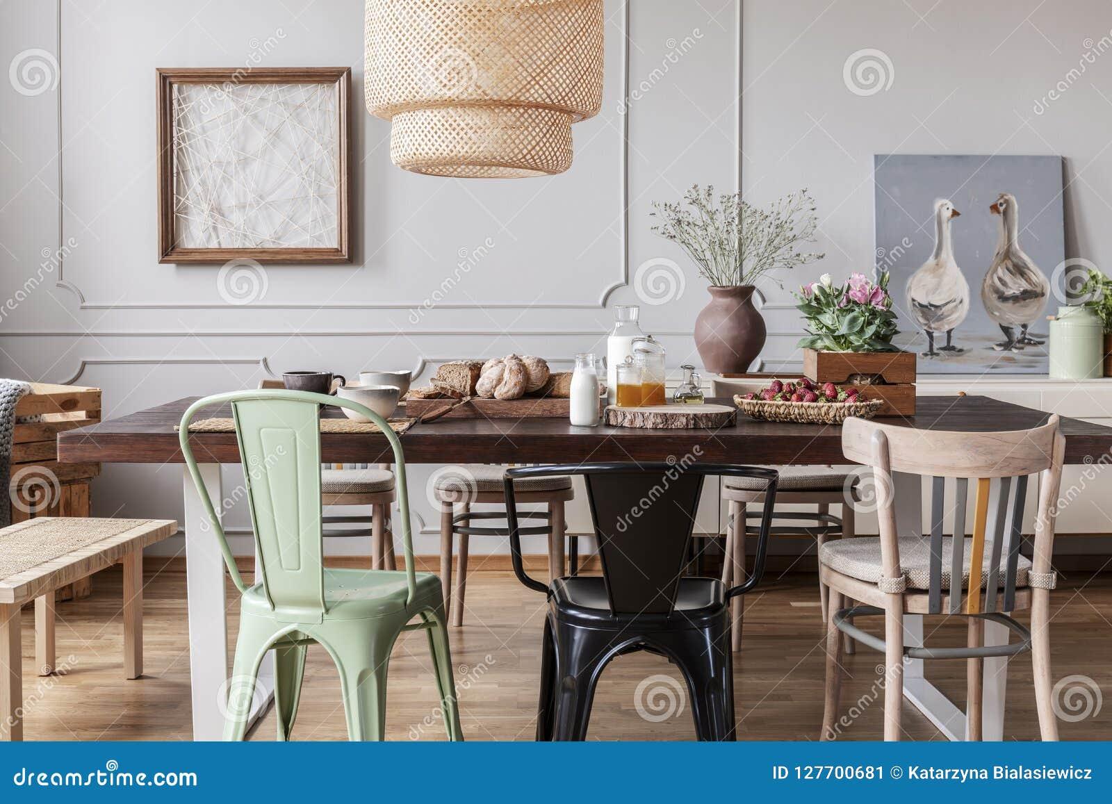 Sillas coloridas en la tabla de madera en interior gris del comedor con los carteles y las flores Foto verdadera
