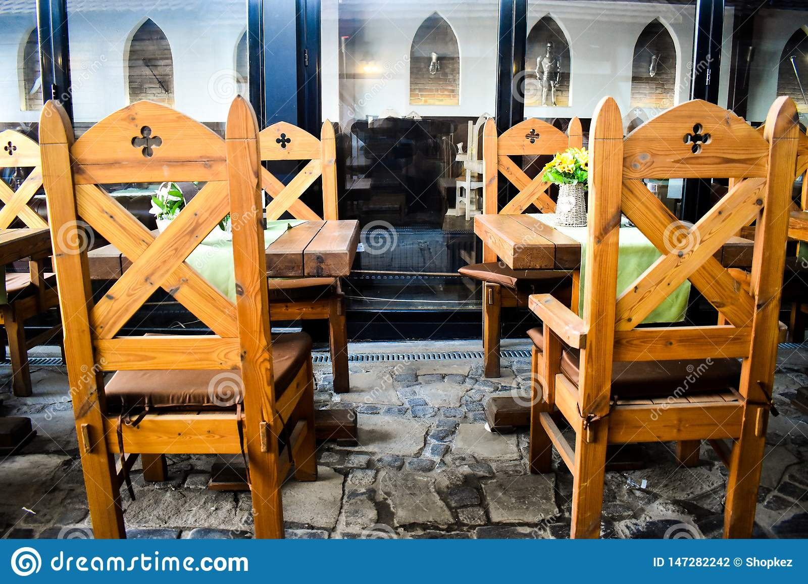 Sillas de madera antiguas con las decoraciones medievales en restaurante del vintage con muchos elementos feudales de la decoraci