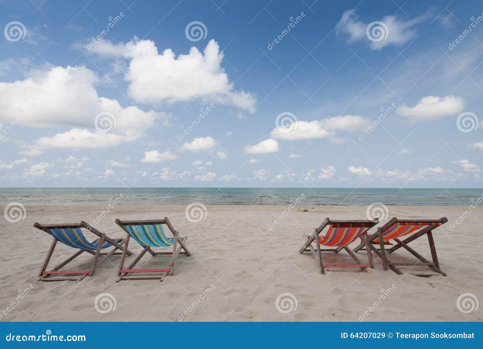 Sillas de playa en la playa blanca de la arena