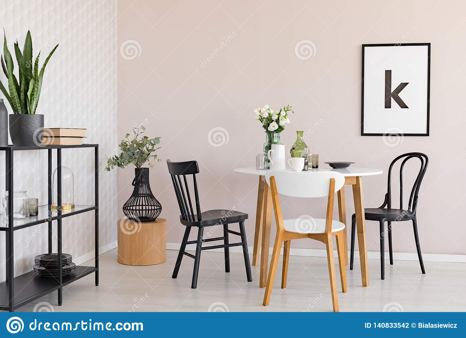 Sillas en la tabla de madera con las flores en el comedor interior con las plantas y el cartel Foto verdadera