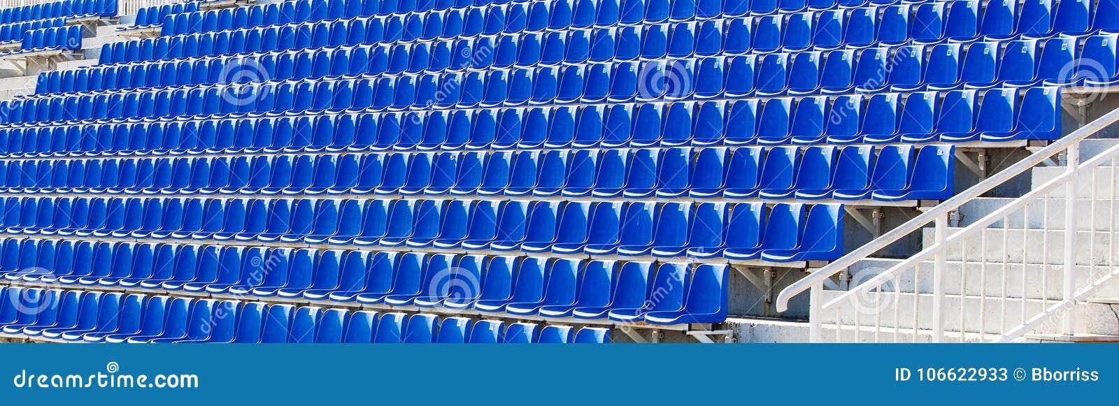 Sillas plásticas azules dobladas en una tribuna temporal
