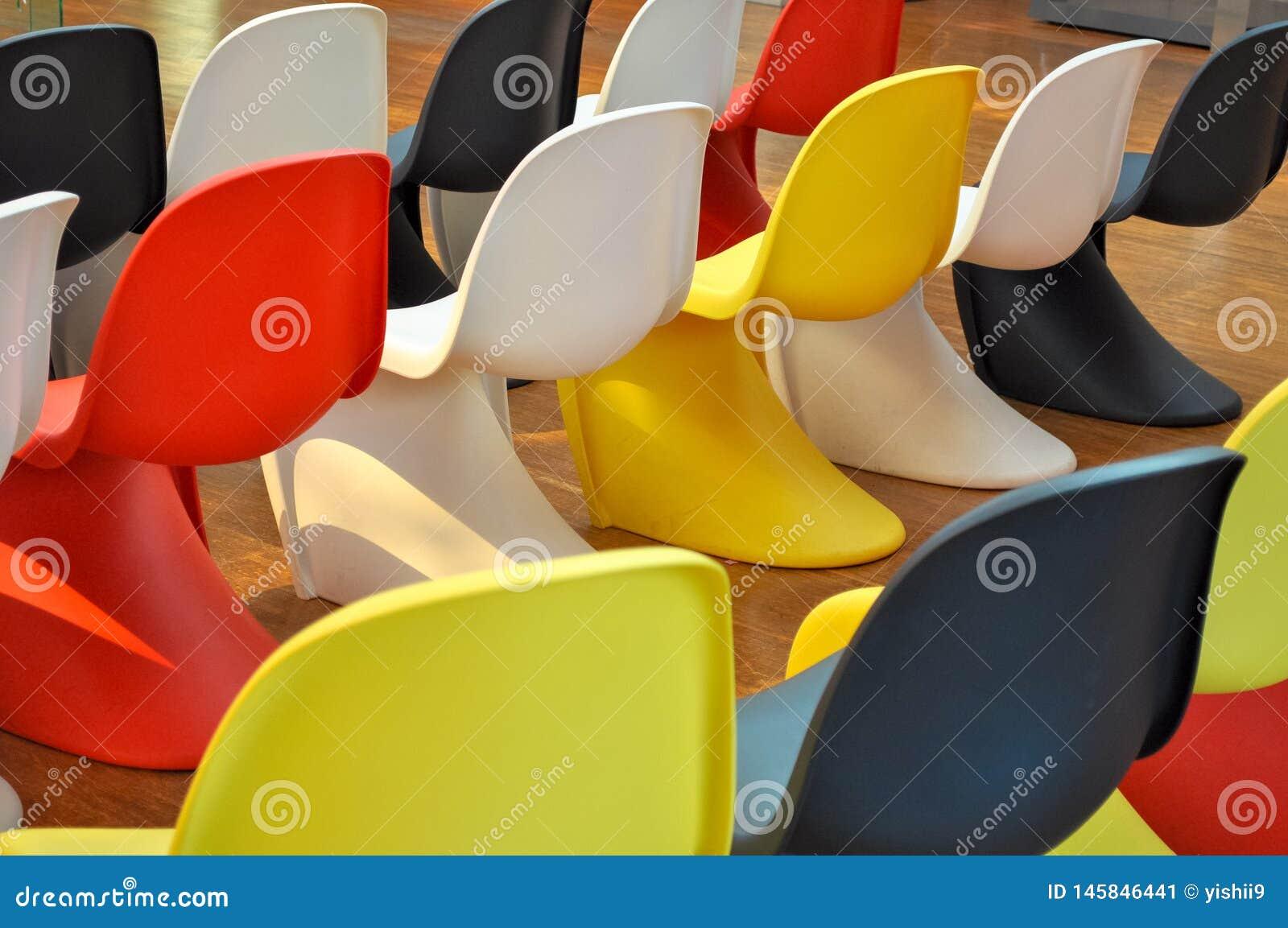 Sillas plásticas coloridas alineadas en un cuarto