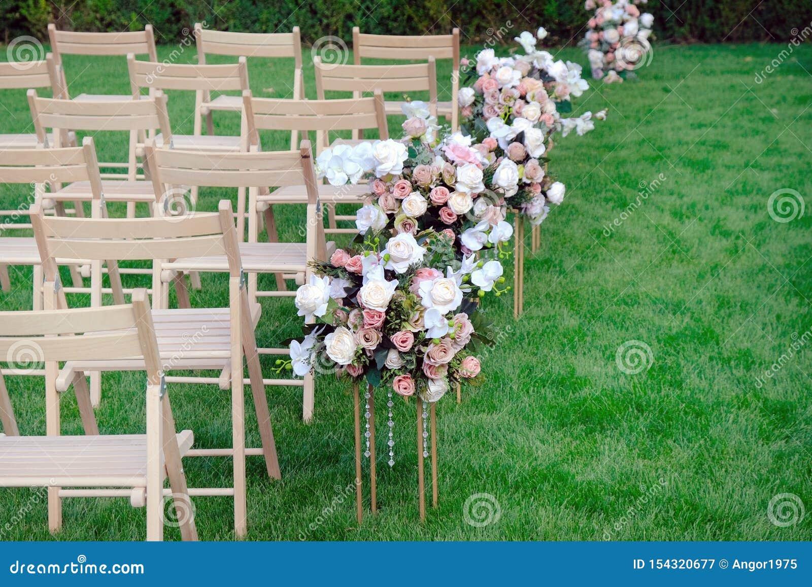 Sillas vacías de madera blancas en fila y ramos de las flores en hierba verde Decoraciones de la ceremonia de boda