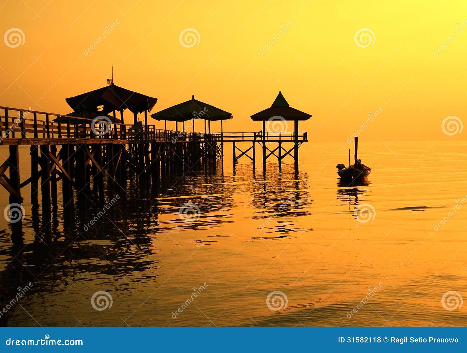 Sillhouette-Pier neben Boot auf dem Ufer
