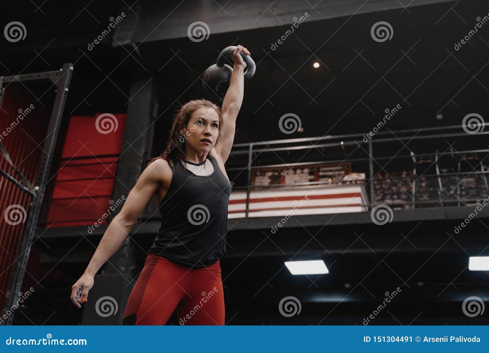 Silna crossfit kobieta ćwiczy z kettlebell przy gym Kobieta robi czynnościowemu szkoleniu