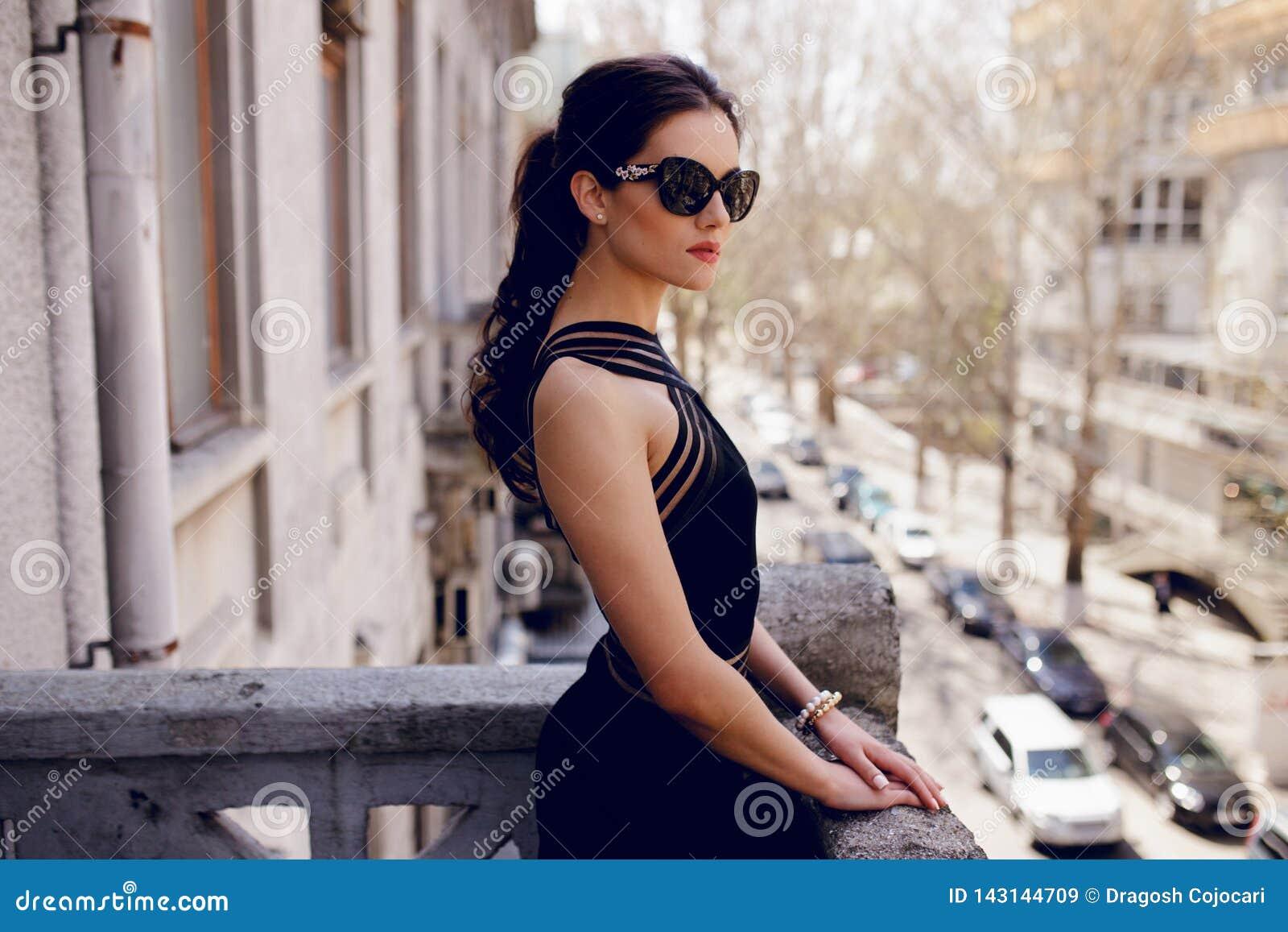 Silna, elegancka kobieta w czarnych okularach przeciwsłonecznych, seksowna czerni suknia, włosiany ponytail, spojrzenia z postawą