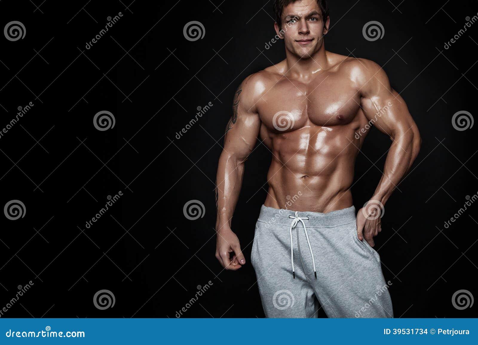 Silna Sportowa mężczyzna sprawności fizycznej modela półpostać pokazuje mięśnie