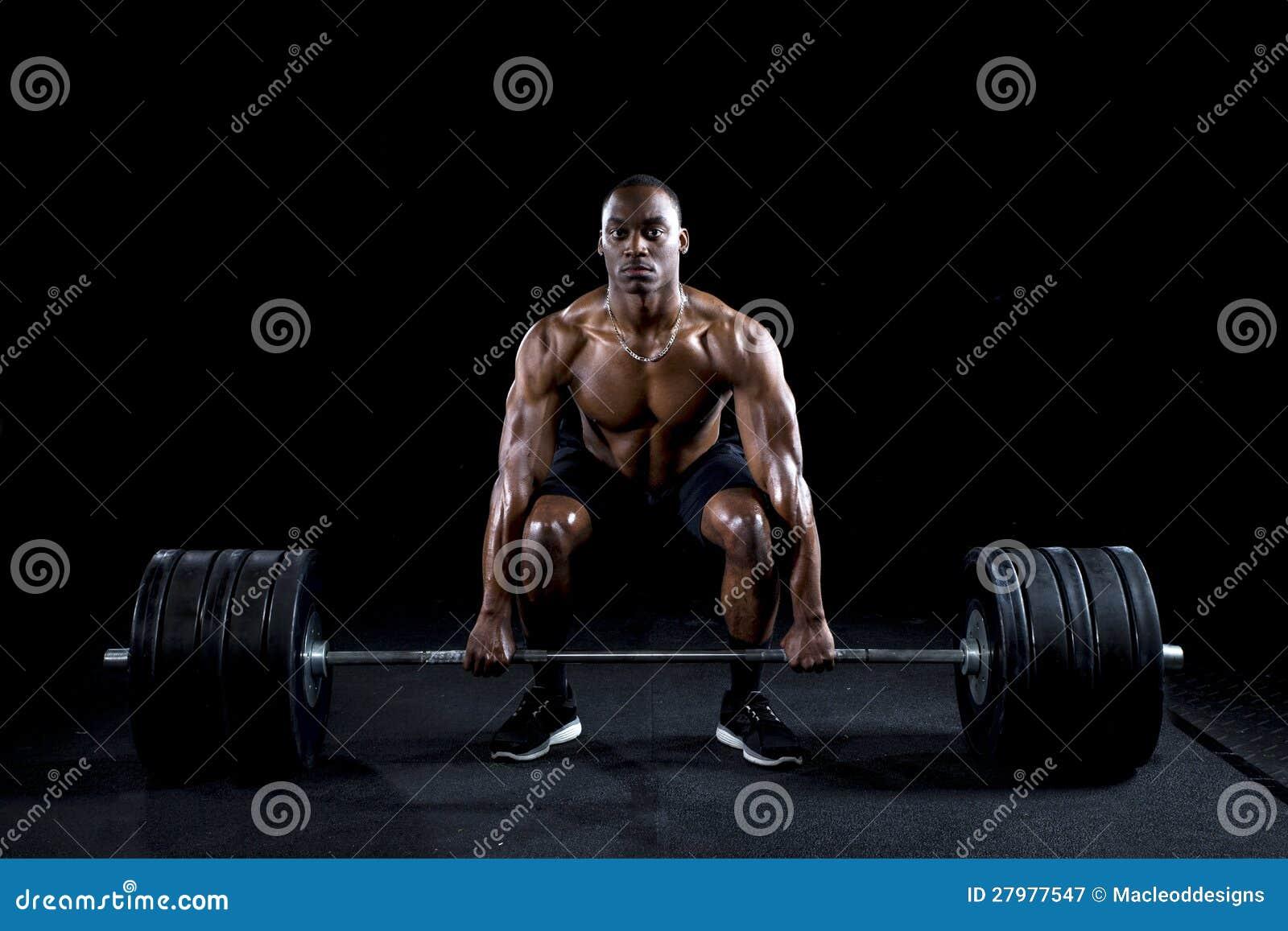 Silni seksowni mężczyzna deadlifts mnóstwo ciężar