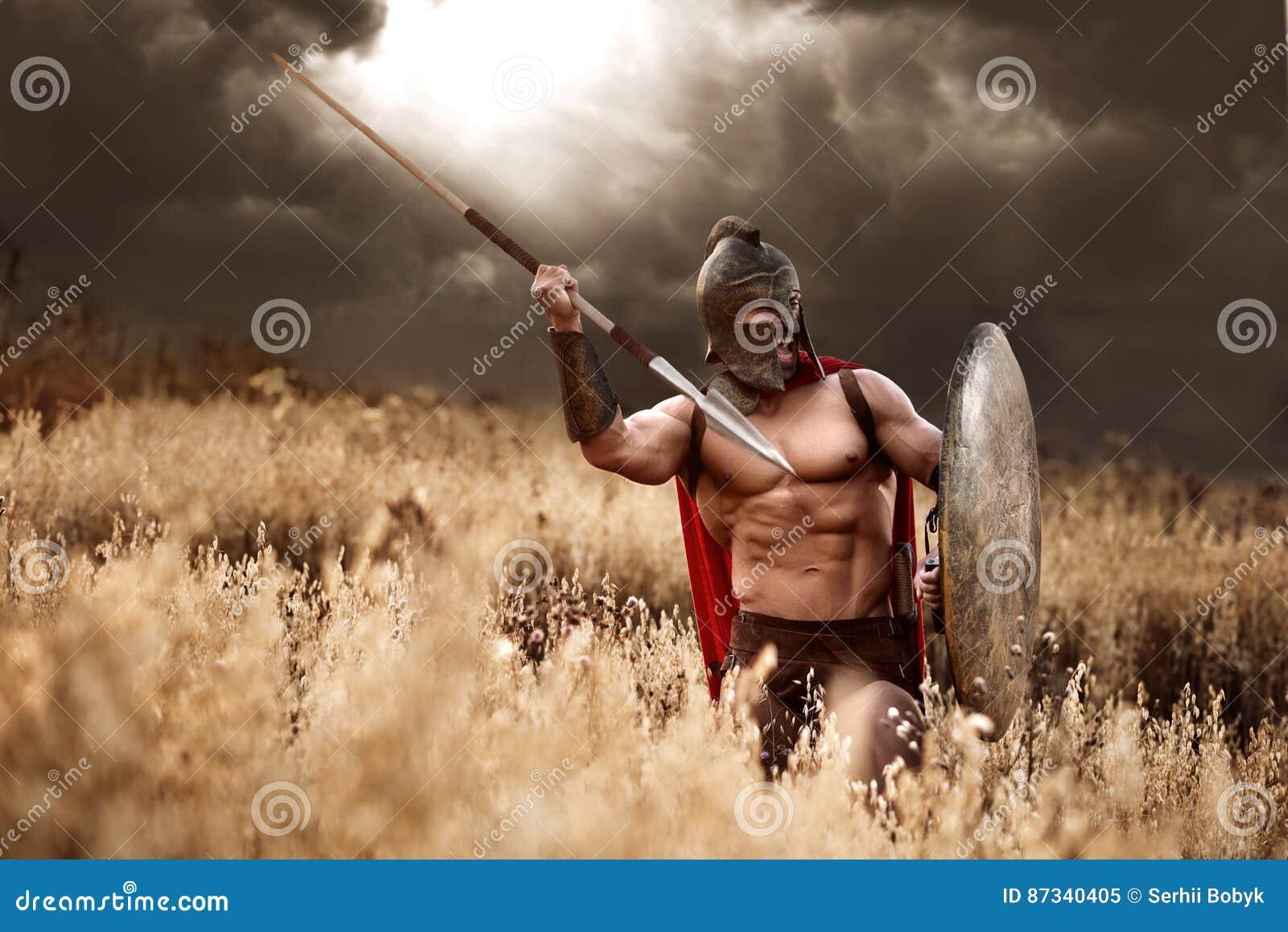 Silny Spartański wojownik w batalistycznej sukni z osłoną i dzidą