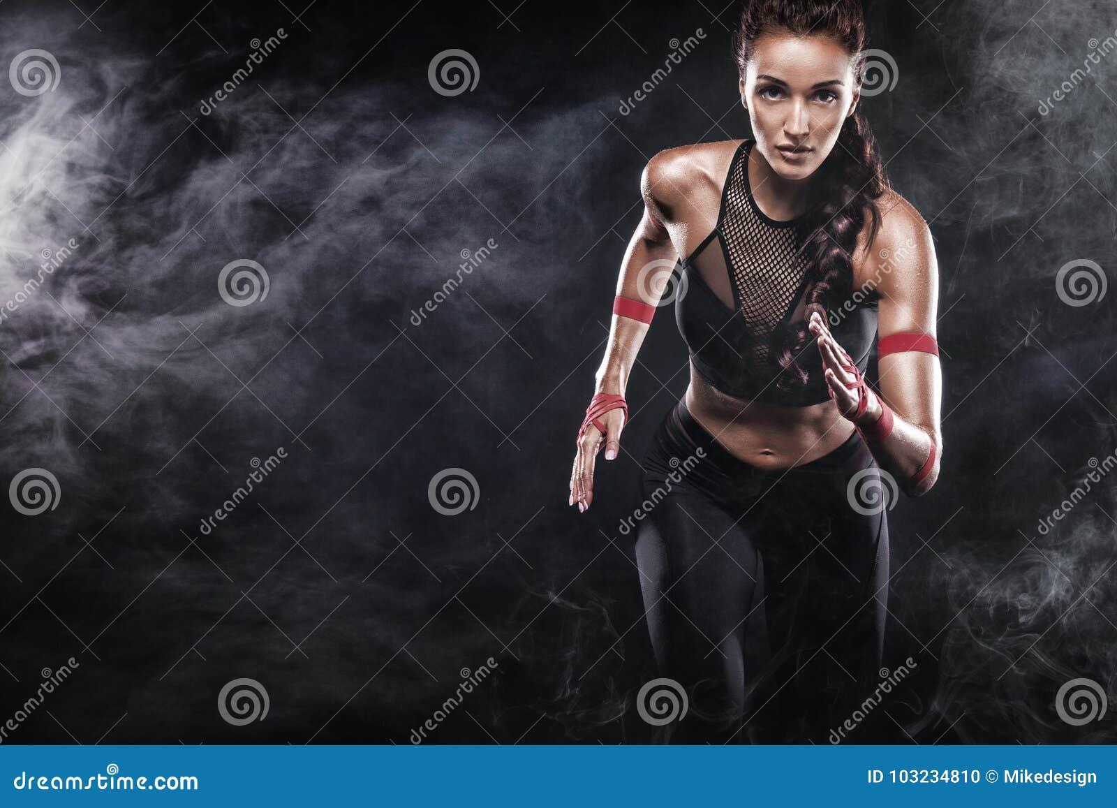 Silny sportowy, kobieta szybkobiegacz, biega na czarnym tle jest ubranym w sportswear, sprawności fizycznej i sporta motywaci,