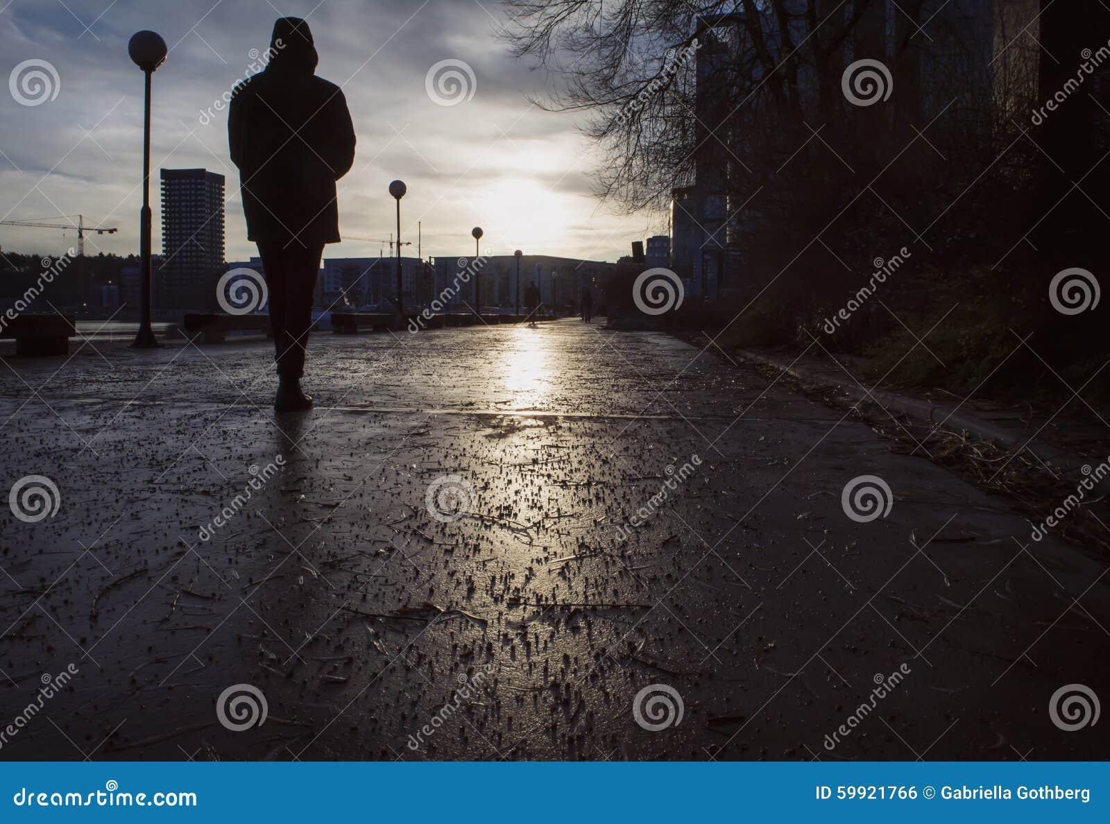 Silohouette του ατόμου που περπατά σε μια υγρή οδό μια θλιβερή ημέρα στα τέλη του φθινοπώρου/το χειμώνα,