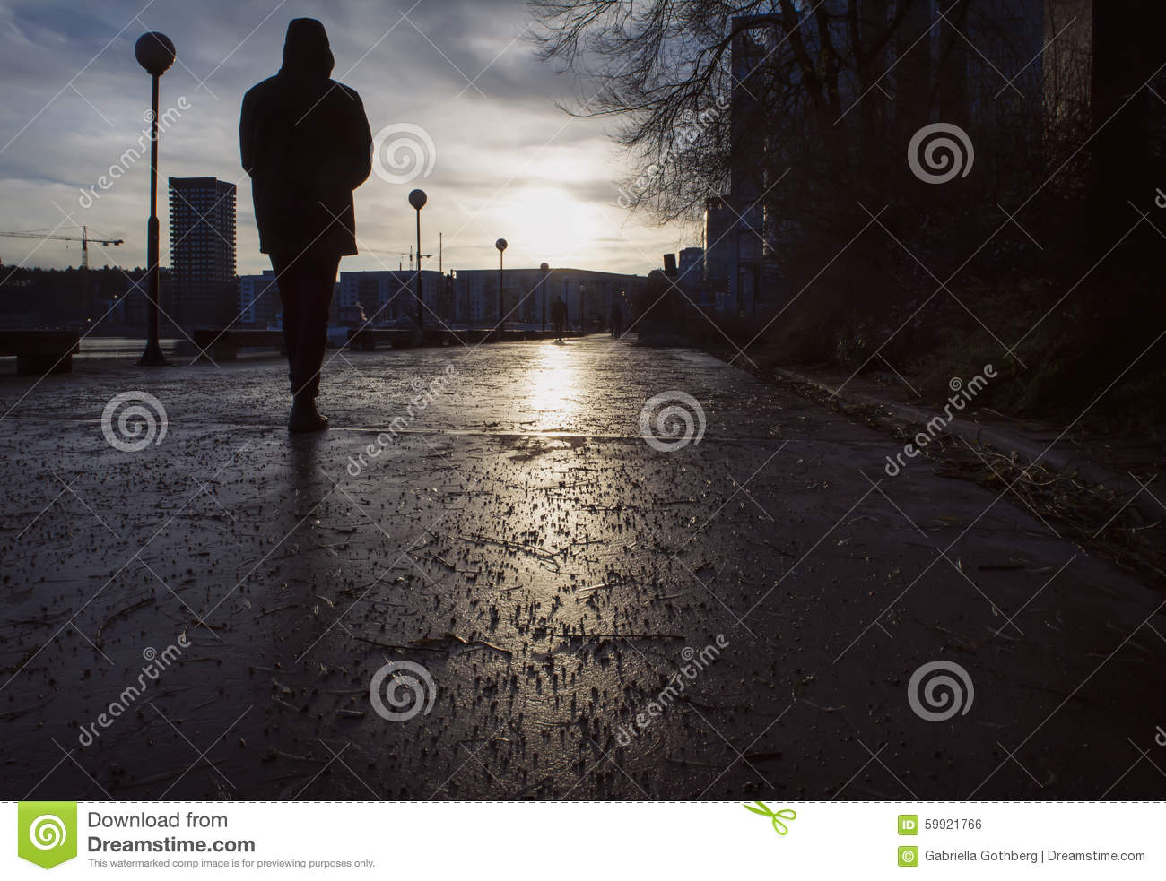 Silhouette of man walking on a damp street a gloomy day in late autumn/winter,